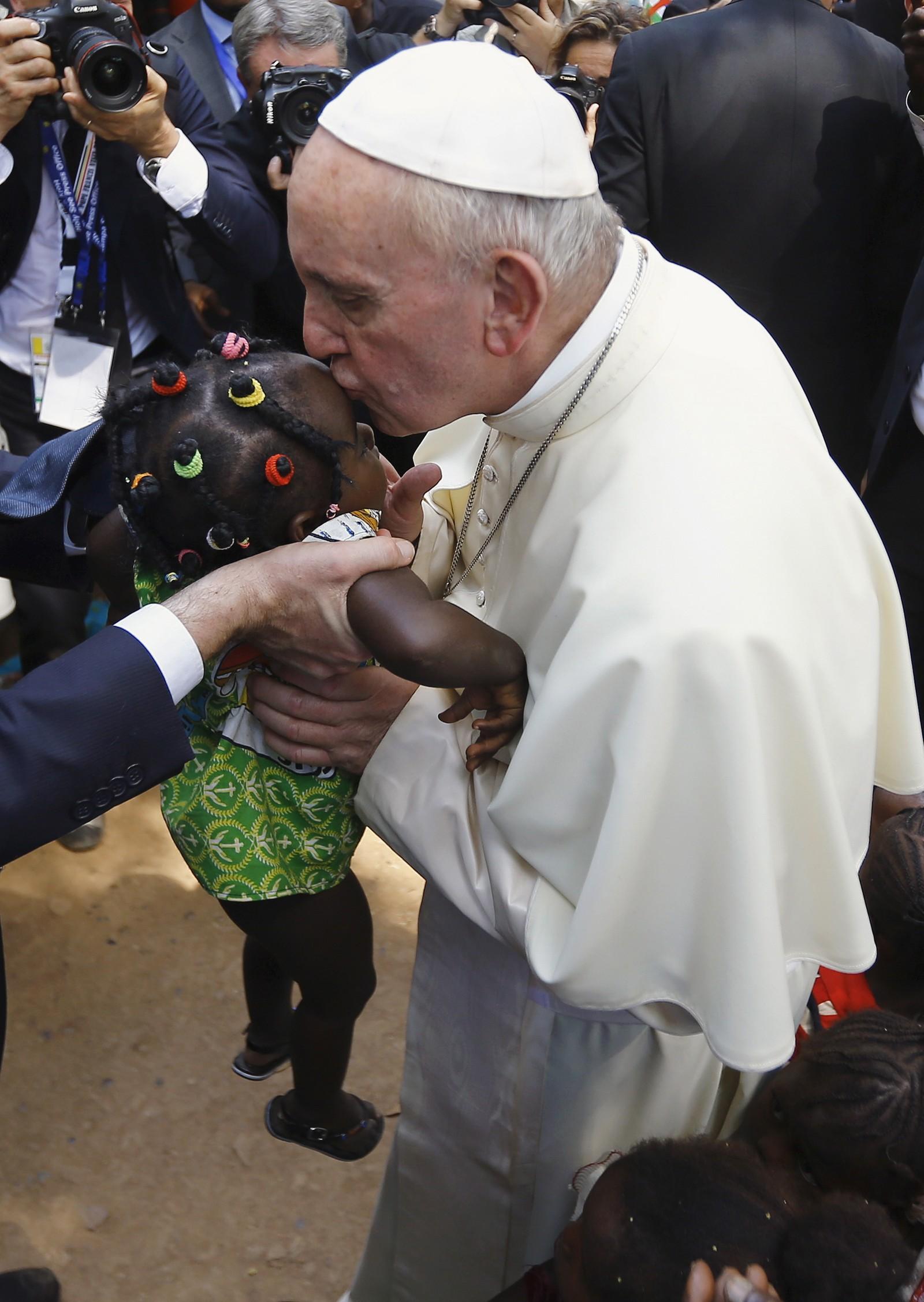 Enda et lite barn får et kyss av paven.