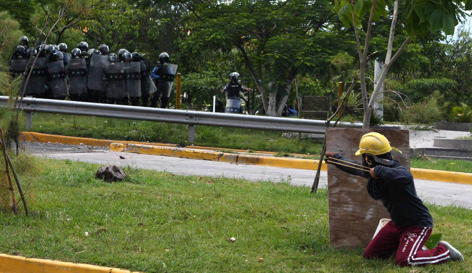 En student, bevæpnet med sprettert, sikter på opprørspolitiet under demonstrasjoner i Tegucigalpa i Honduras torsdag. Studentorganisasjonen har siden 30. juni okkupert flere bygninger ved det offentlige universitetet i Honduras (UNAH), og dermed hindret rundt 50.000 studenter fra å delta i undervisningen. Studentorganisasjonen krever blant annet at universitetets rektor Julieta Castellanos må gå av.