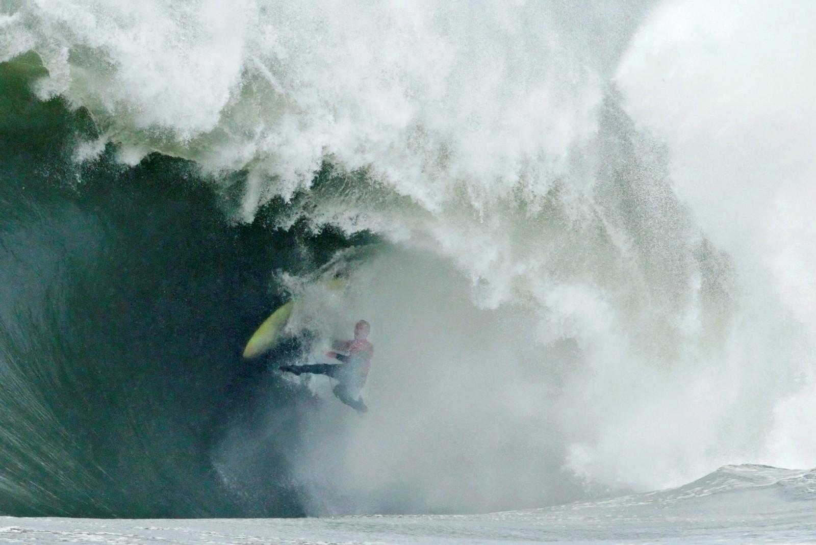 Den australske surferen Justen Allport blir tatt av bølgen under en surfekonkurranse ved Cape Solander i Sydney mandag.