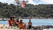 Turister ser på skogbrann i La Croix-Valmer - Foto: VALERY HACHE/AFP