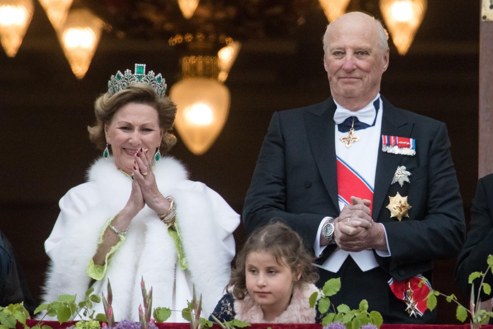 Dronning Sonja (t.v.), Emma Tallulah Behn og kong Harald. Kongeparet med kongelige gjester hilser publikum fra slottsbalkongen i anledning sin 80-årsfeiring.