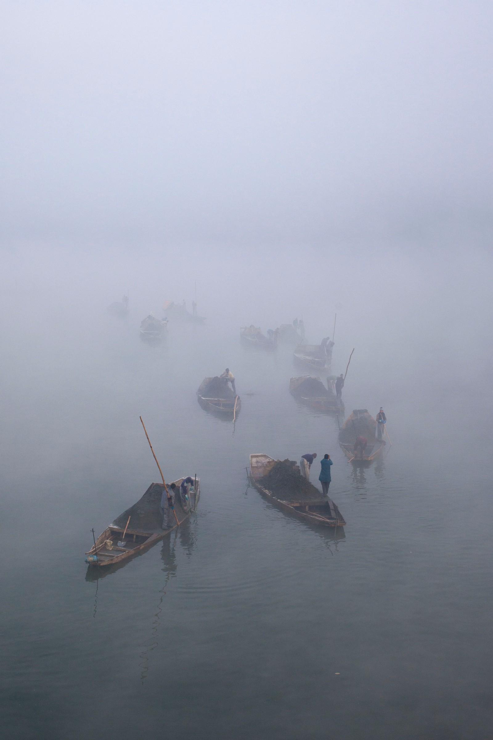 Båtmenn fra Kashmir samler sand i elva Jhelum omringa av tåke. Den indiske delen av Kashmir har opplevd lave temperaturer i det siste.
