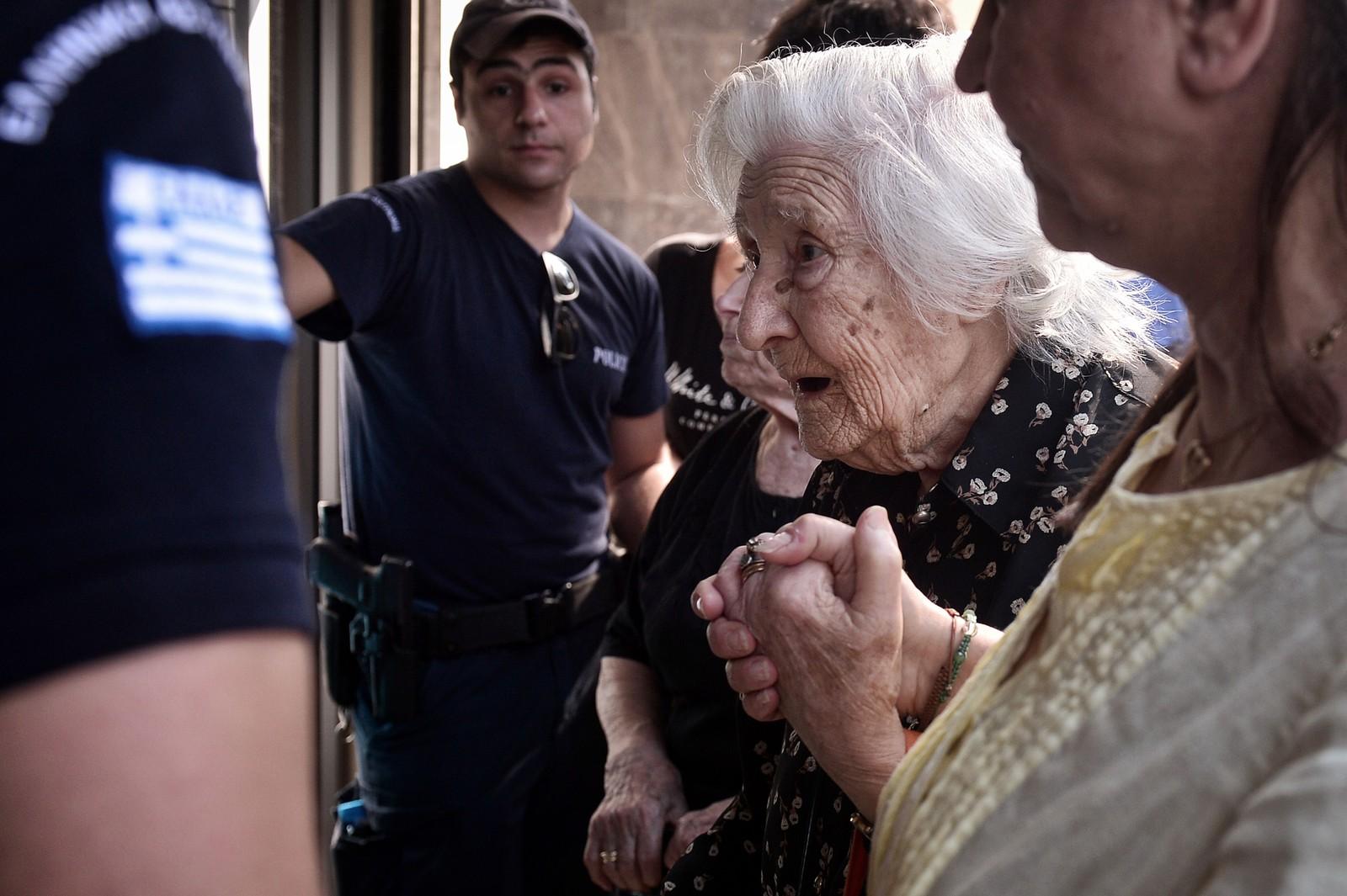 En kvinne følger sin eldre mor for at hun skal få ta ut penger i en bank i Aten.