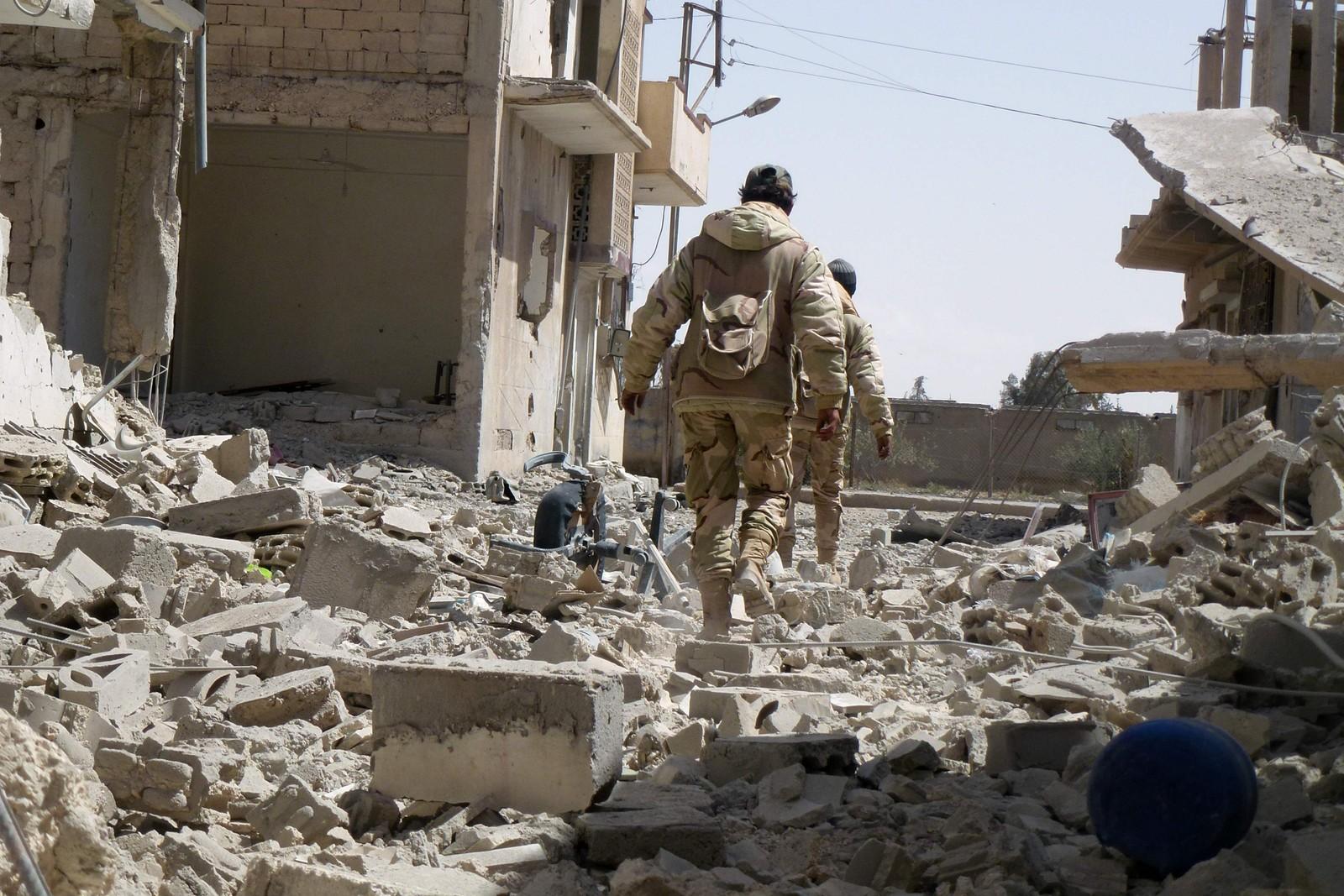 Syriske tropper går i de ødelagte gatene i den moderne delen av Palmyra etter at de gjenerobret UNESCO-området fra IS 27.mars.