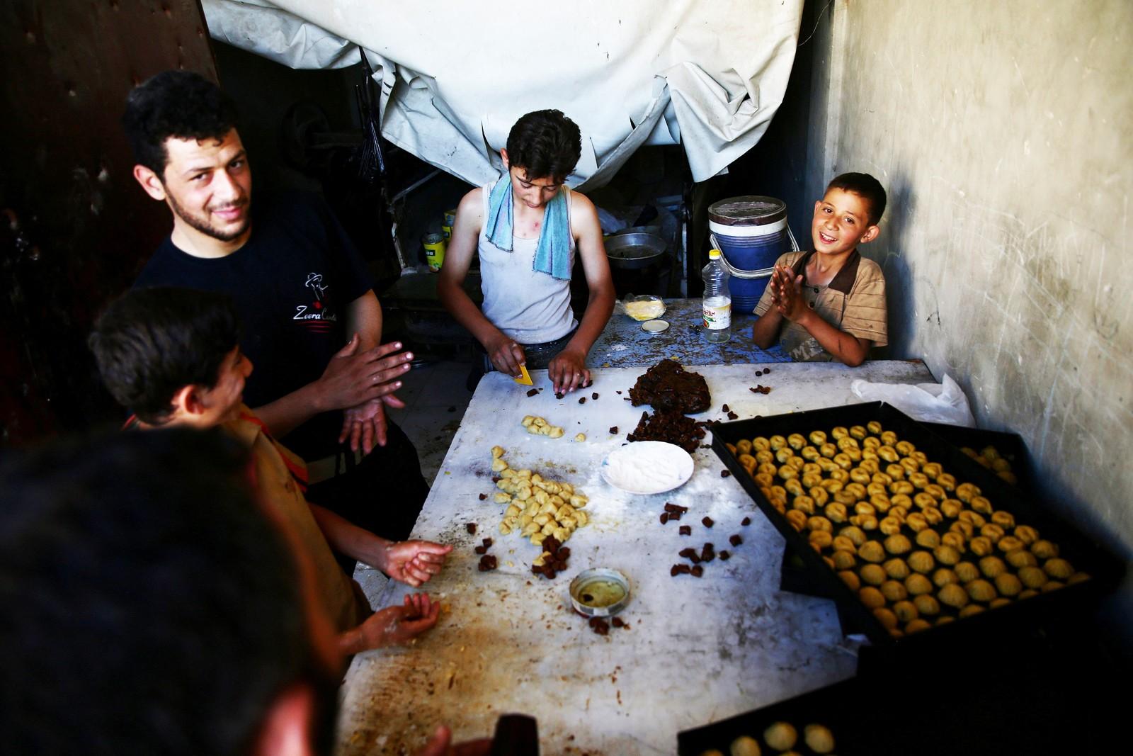 DAMASKUS: Gutter og menn lager tradisjonelle søtsaker som skal brukes under Eid-feiringen. BIldet er tatt i bydelen Douma i øst-Ghouta i hovedstaden Damaskus i Syria.