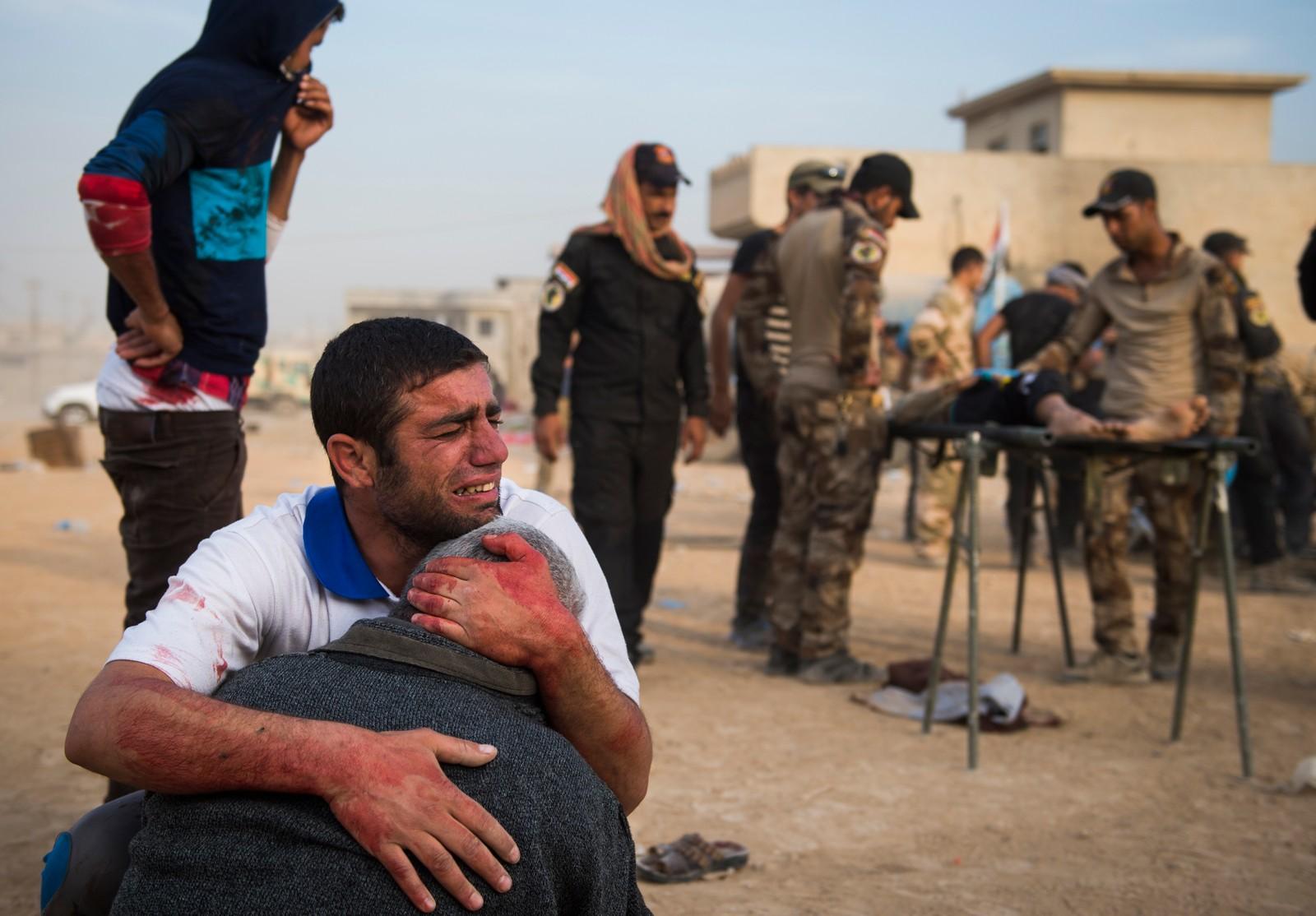 1. plass Nyhetsreportasje utland: Odd Reidar Andersen, AFP.  Irakiske regjeringsstyrker kjemper mot IS-militsen for kontroll over den nord-irakiske byen. Elitestyrkene kommer under ild når de rykker frem i nabolaget Karkukli. Far og bestefar til 15 år gamle Shafiq sørger, etter at Shafiq og vennen Mohammed mistet livet.