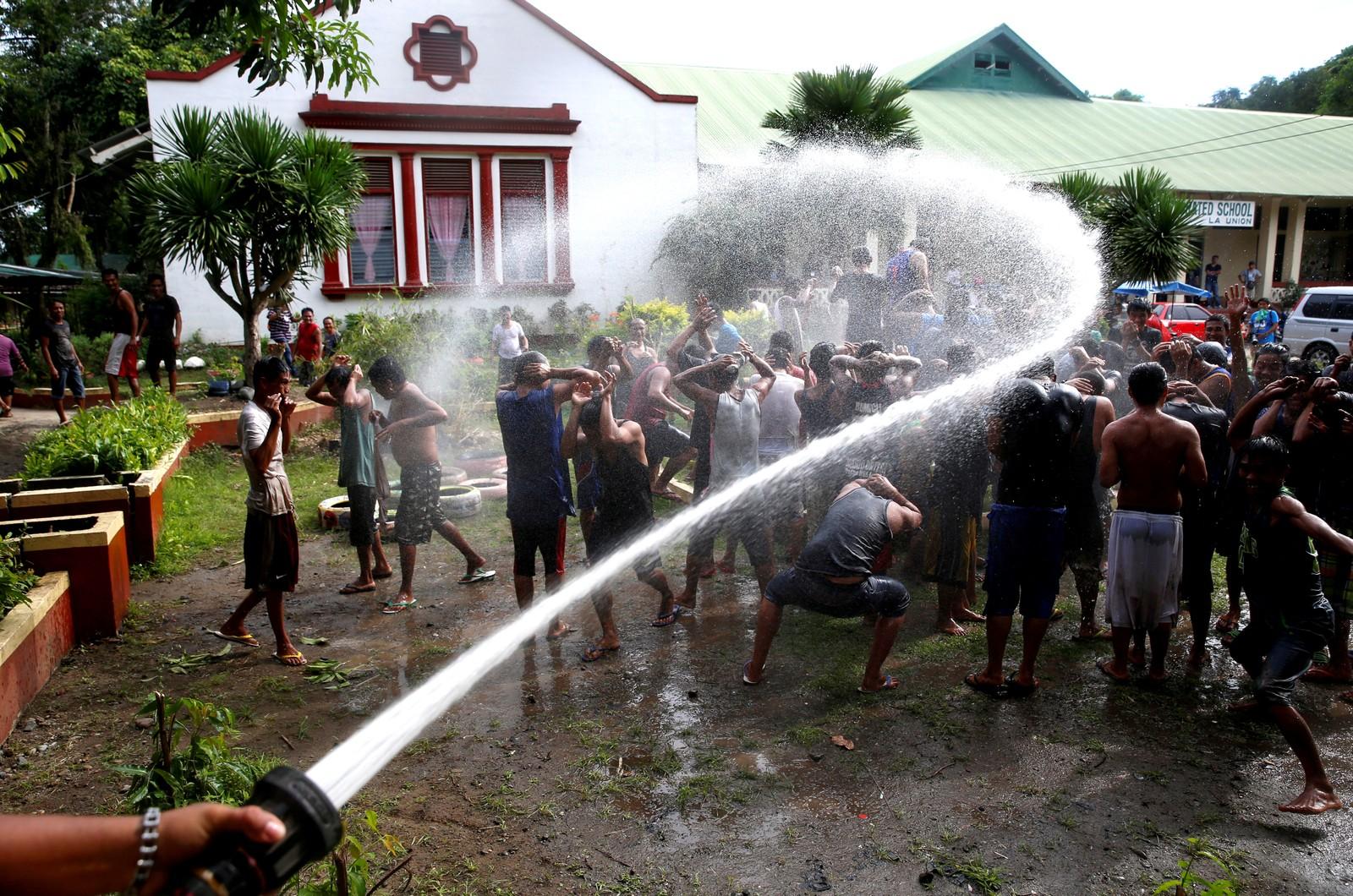 Narkotikabrukere som kaller seg «Recovering Champions», spyles med vann som en del av et rehabiliteringsprogram nord på Filippinene.