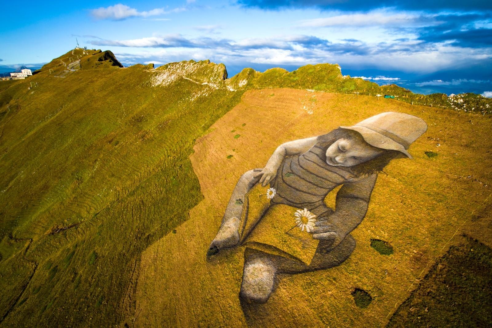 """Dette gigantiske verket, et eksempel på noe som blir kalt """"stedskunst"""", er laget av den franske kunstneren Sapye og er omtrent 6000 kvadratmeter stort. Maleriet er laget av naturlige pigmenter, vann og et melkeprotein som gjør at det brytes naturlig ned. Verket heter """"A Story of the Future"""" og ligger på en fjellside i Les Rochers-de-Naye i Sveits."""