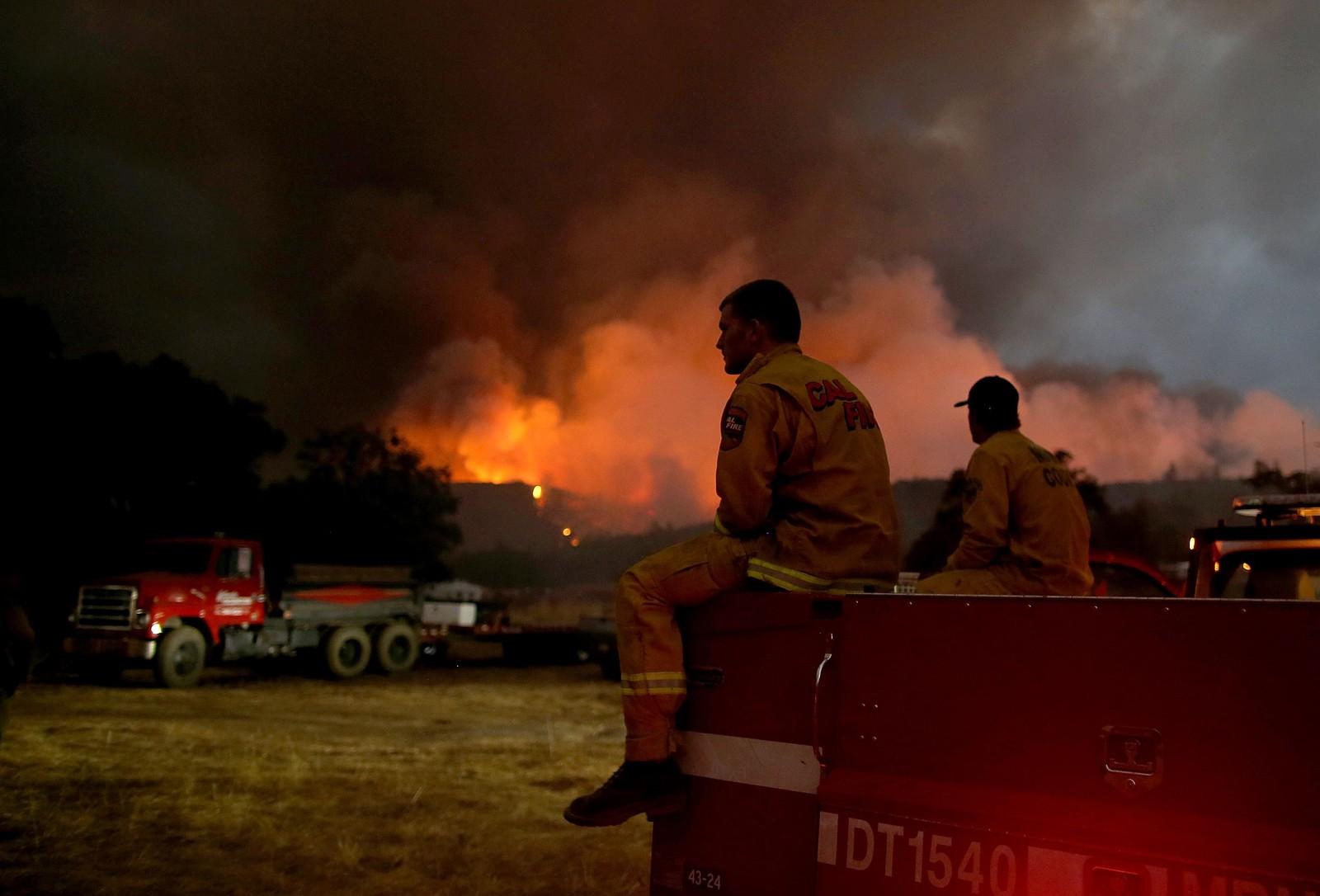 Brannmenn tar en liten pause fra det krevende slukkingsarbeidet ved skogbrannen i Lower Lake i California.