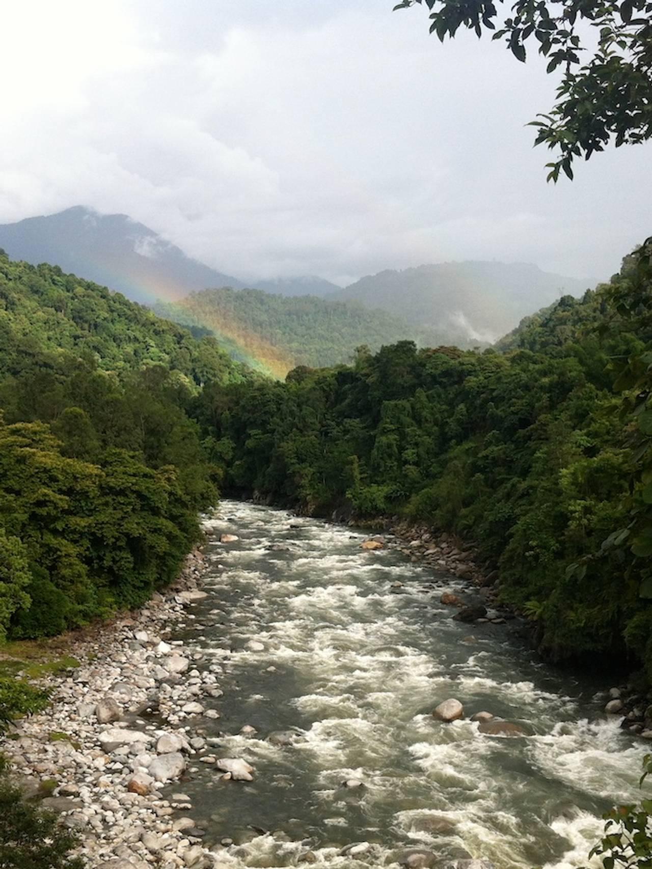 Elv i Himalaya med regnbue  i retning av fjellene