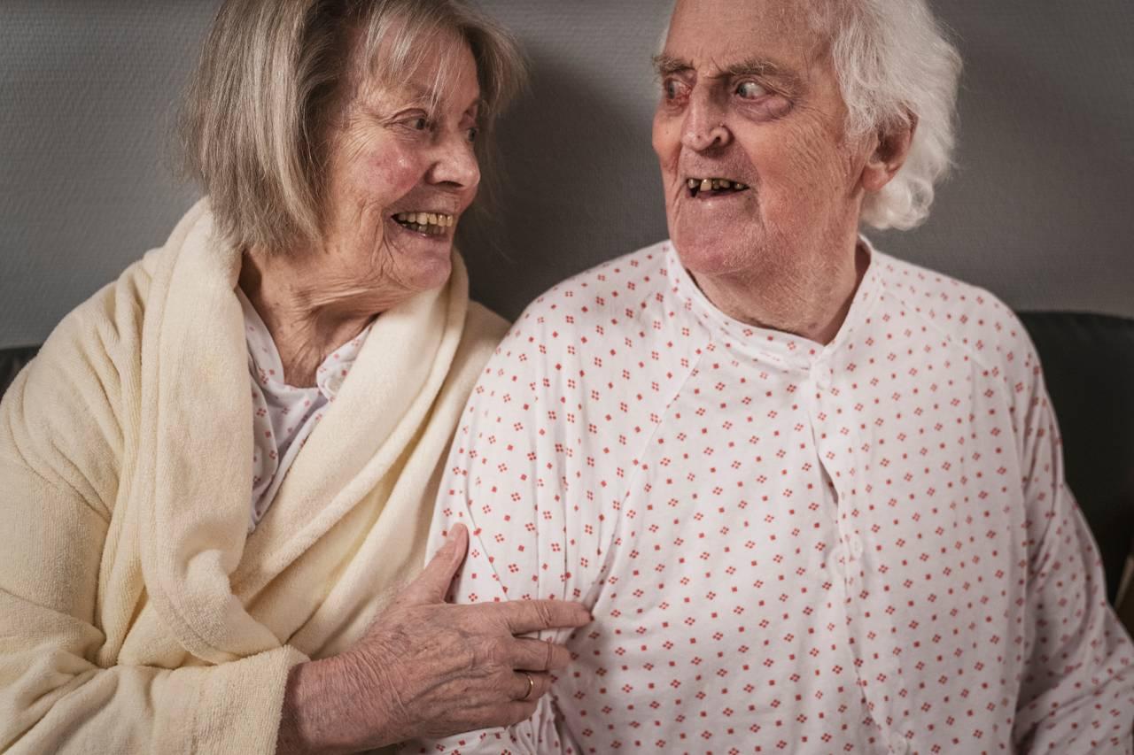 Ekteparet sitter sammen og ser hverandre i øynene. Hun holder hånden fast i armen hans