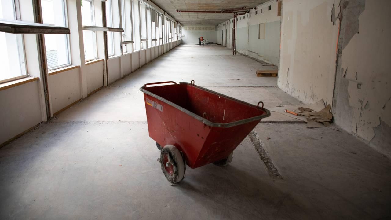 Veggene er borte, og rommet er åpent og strekker seg langt innover. På venstre side skinner dagslyset inn gjennom vinduene. Vegger, gulv og tak er av betong. I taket skimter man noen rør her og der. På gulvet står det en tom tralle.