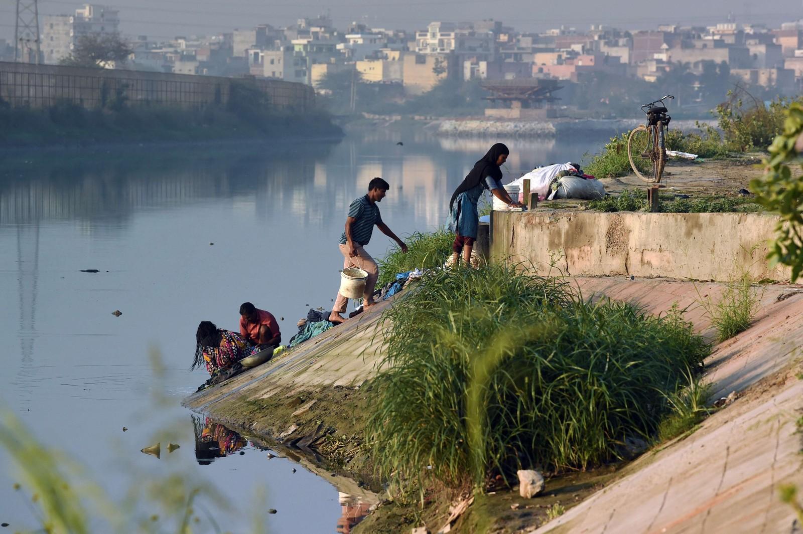 Innbyggere vasker klær i elven i New Dehli, India.