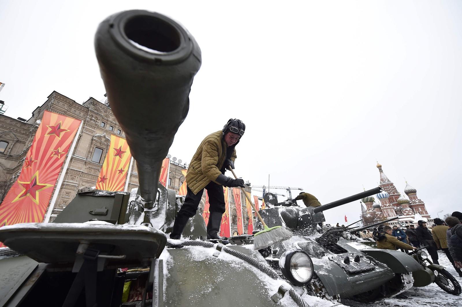 Ein soldat kledd i historisk uniform måker snø av ein restaurert tanks frå andre verdskrigen.