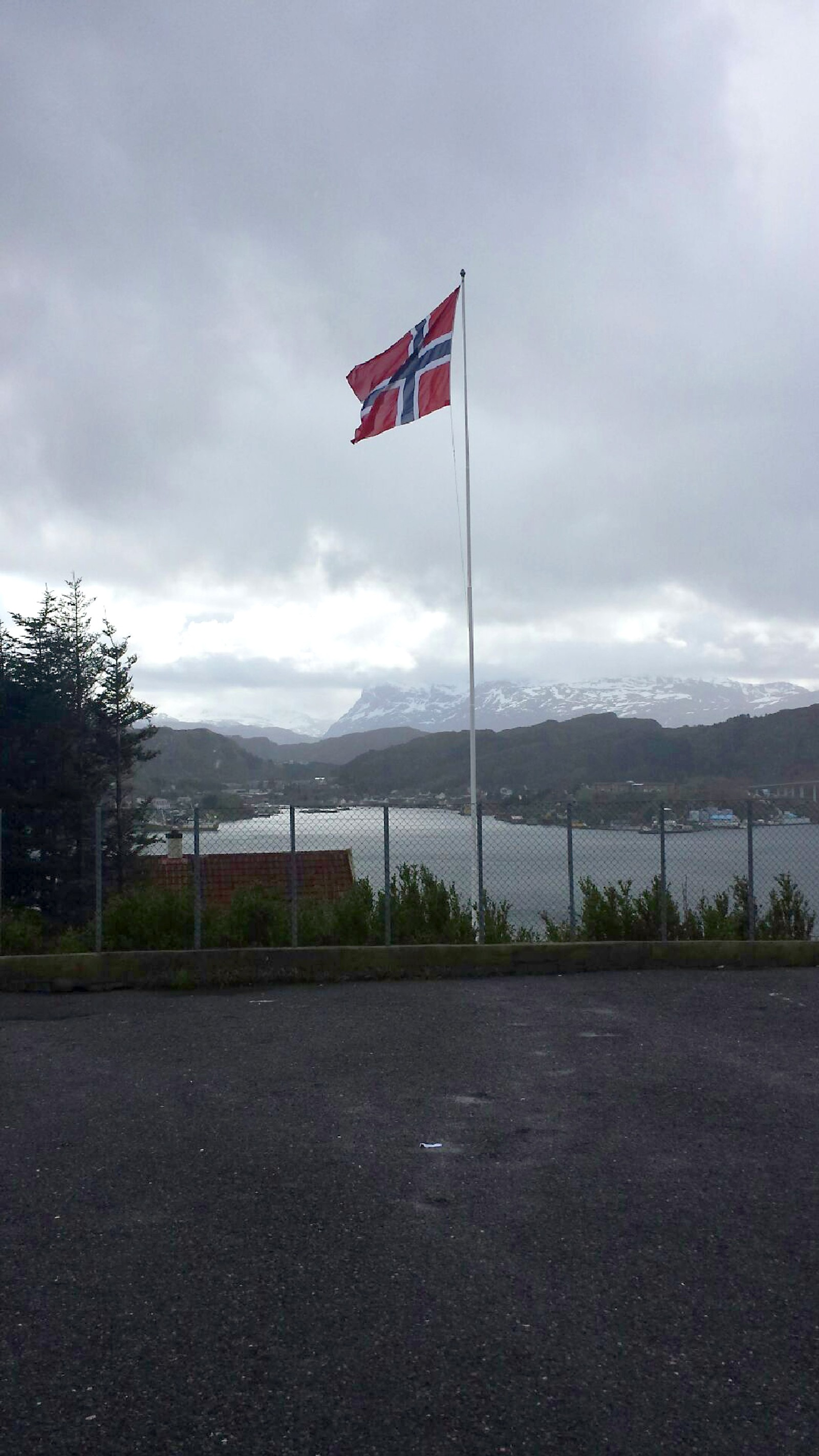 Flagget til Vågsøy ungdomsskole veier frisk i vinden med ein tåketung Hornelen i bakgrunnen.