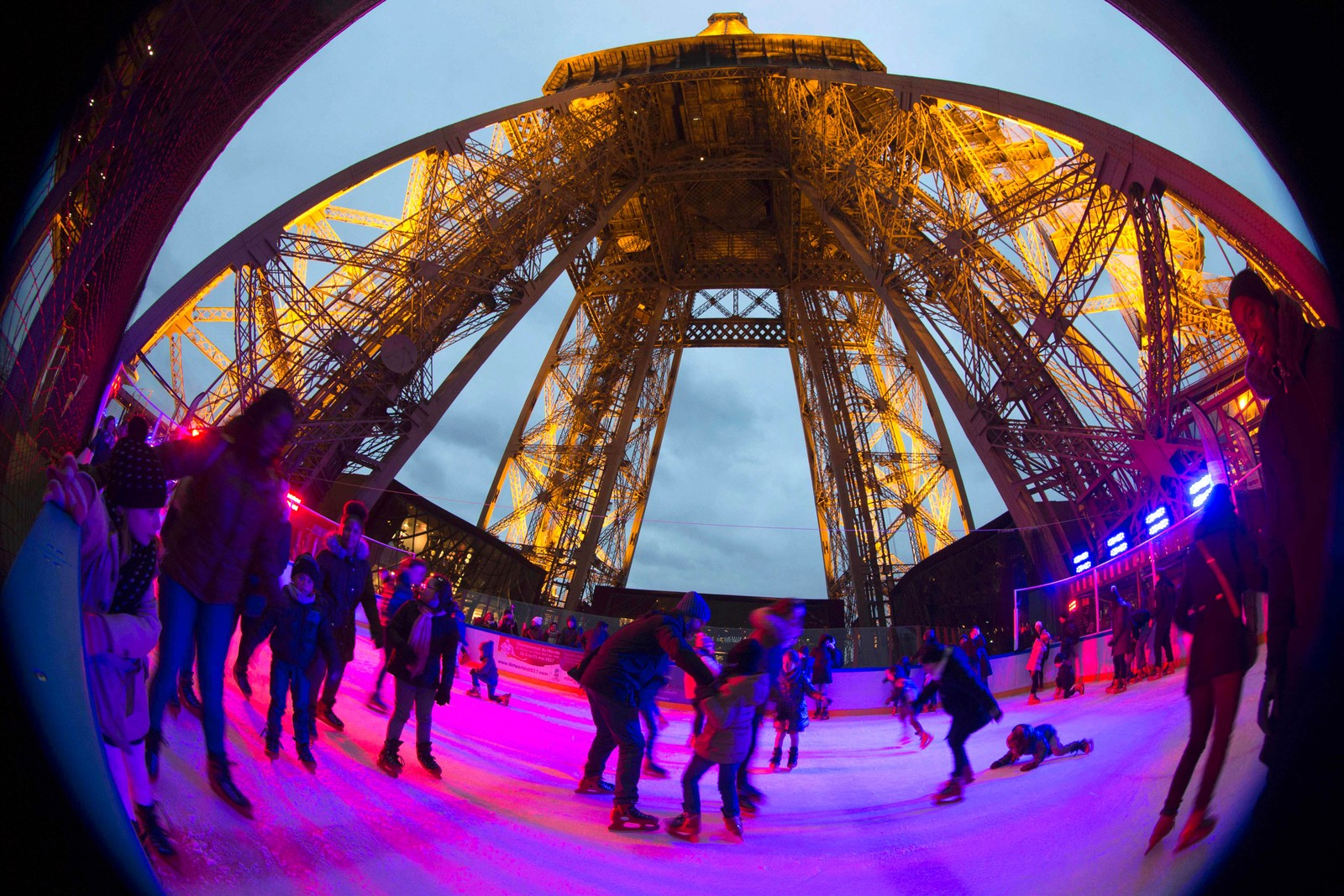 Mennesker koser seg på isen som ligger på Eiffeltårnets første etasje. Isen ligger 57 meter over bakken.
