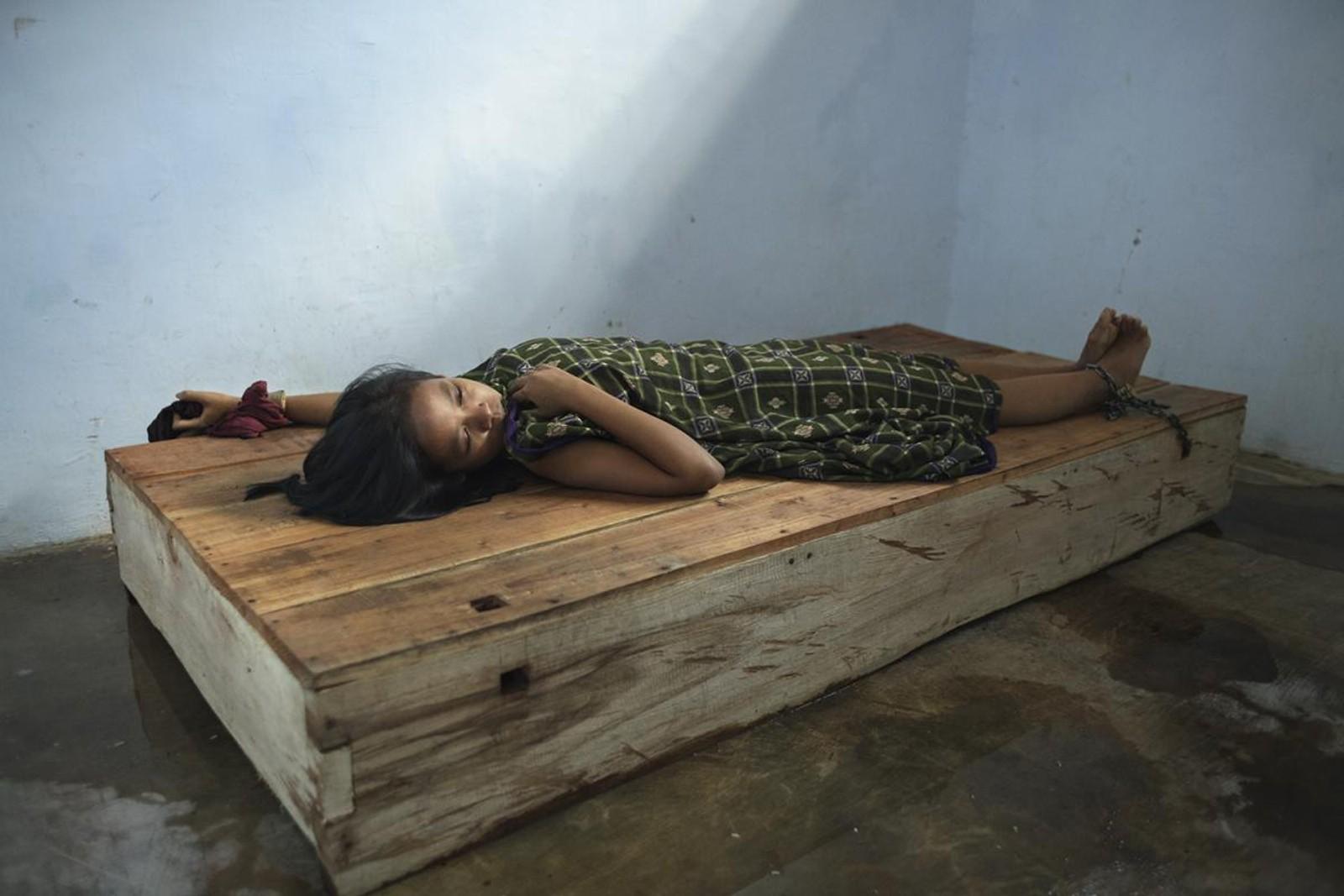 Denne kvinnen er 24 år gammel. Hun har en hånd og en ankel lenket fast til tresengen i Bina Lestari healingsenter i Brebes på øya Java. Etter at ektemannen forlot henne og hennes 5 år gamle datter, utviklet hun depresjon. I Indonesia tror flere at dette betyr at man er besatt av onde ånder.