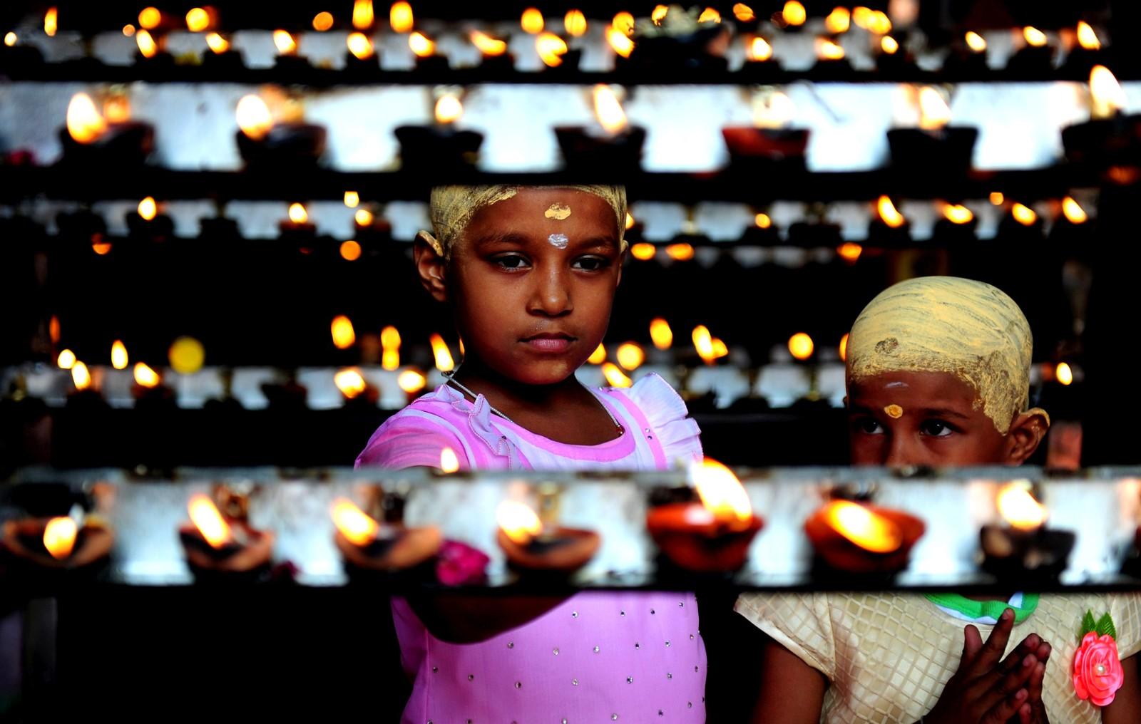 """Indiske hinduer tenner lys under markeringen av """"Aadi Khiruthigai"""" ved Vadapalani Murugan-tempelet i Chennai i India den 28. juli. Aadi er den fjerde måneden i den tamilske kalenderen, og blir regnet for å være hellig. Måneden feires med ritualer hvor de dyrker gudene."""