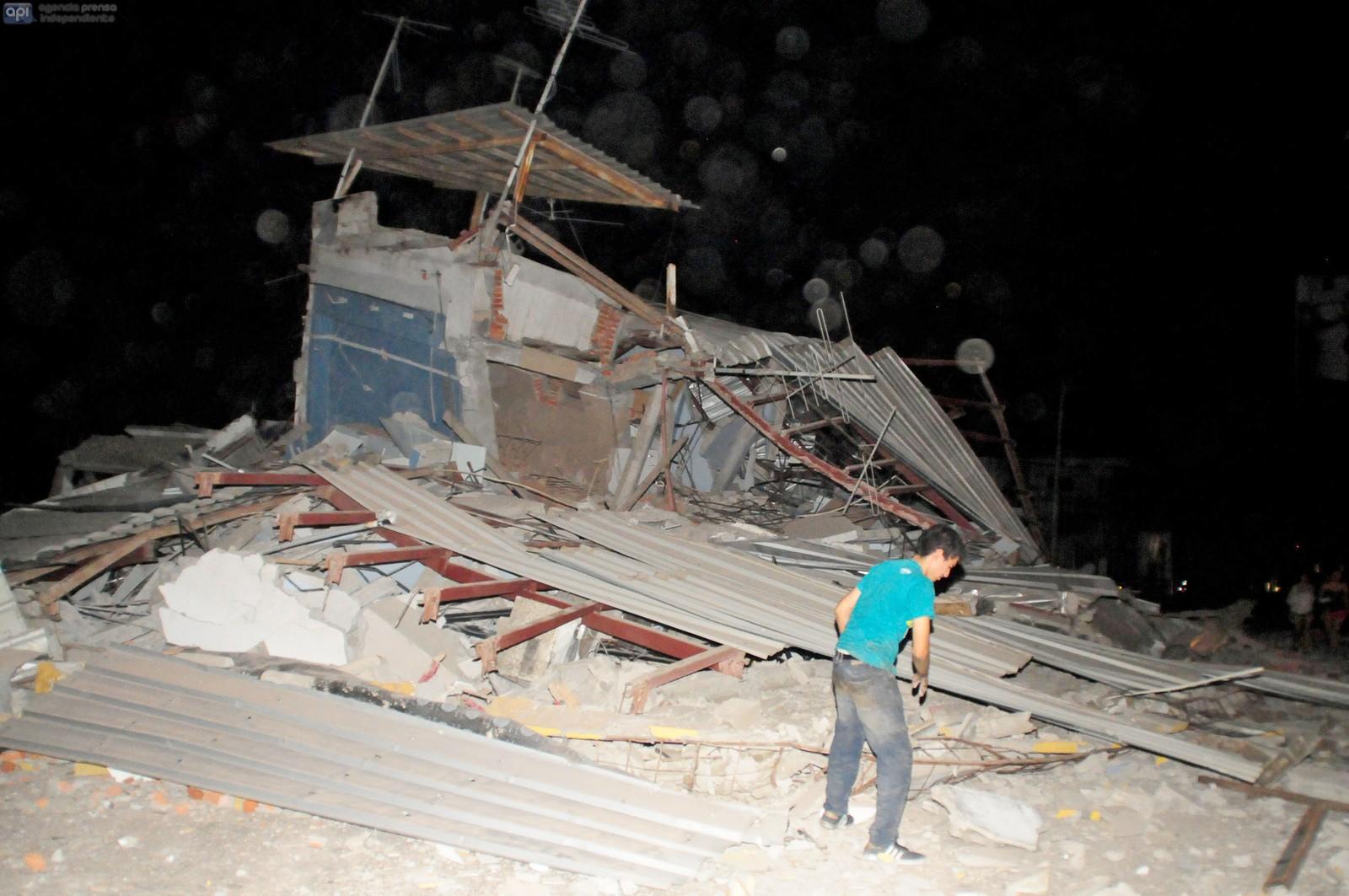 En mann står ved en skadet bygning i Guayaquil.