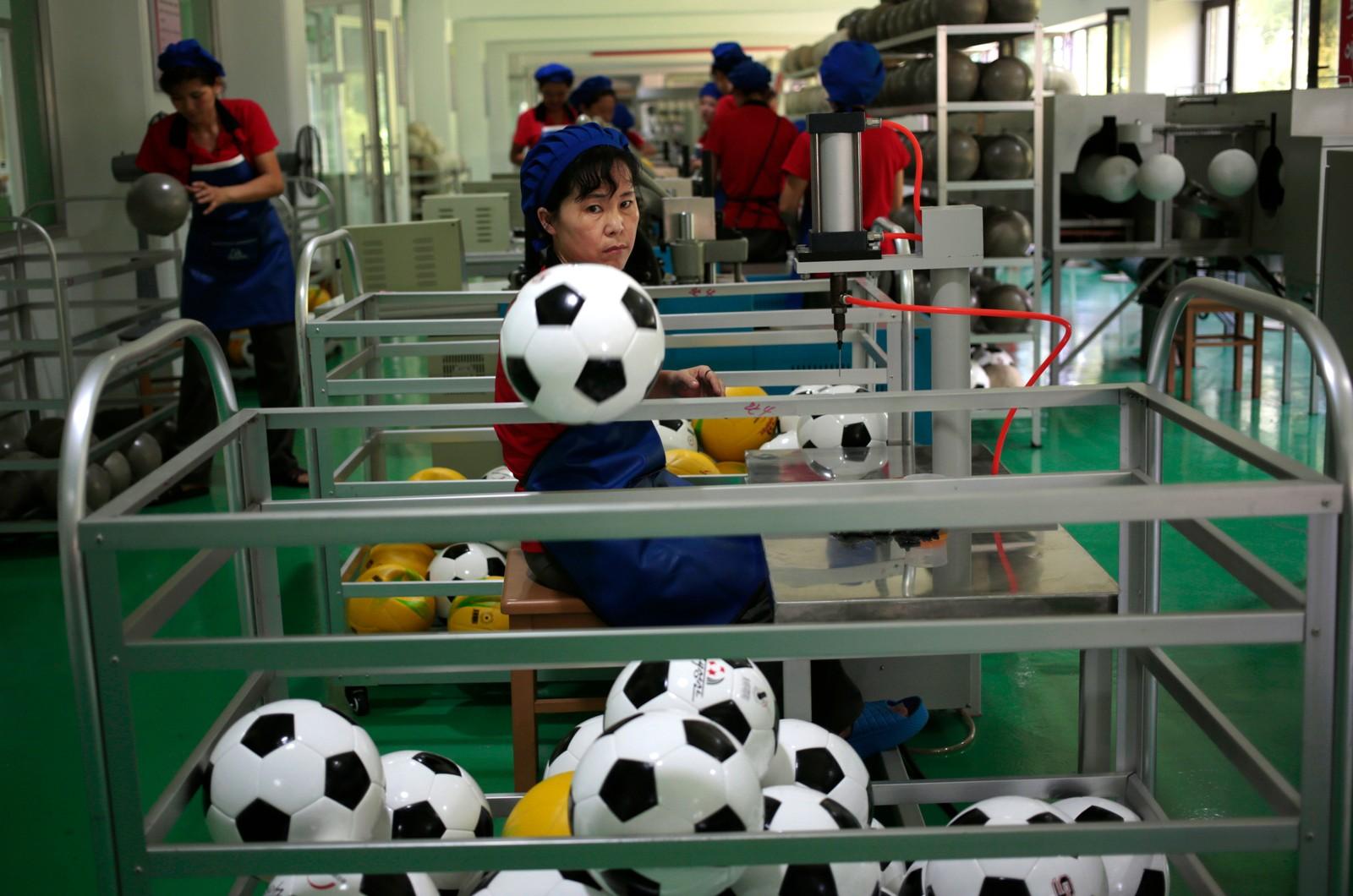 """En kvinne sorterer fotballer på en nyåpnet fabrikk i Pyongyang i Nord-Korea den 22. august. Nord-Korea tok """"bare"""" to gullmedaljer under OL i Rio, men Kim Jong-Un skal være helt bestemt på at landet skal bli en internasjonal sportssupermakt."""