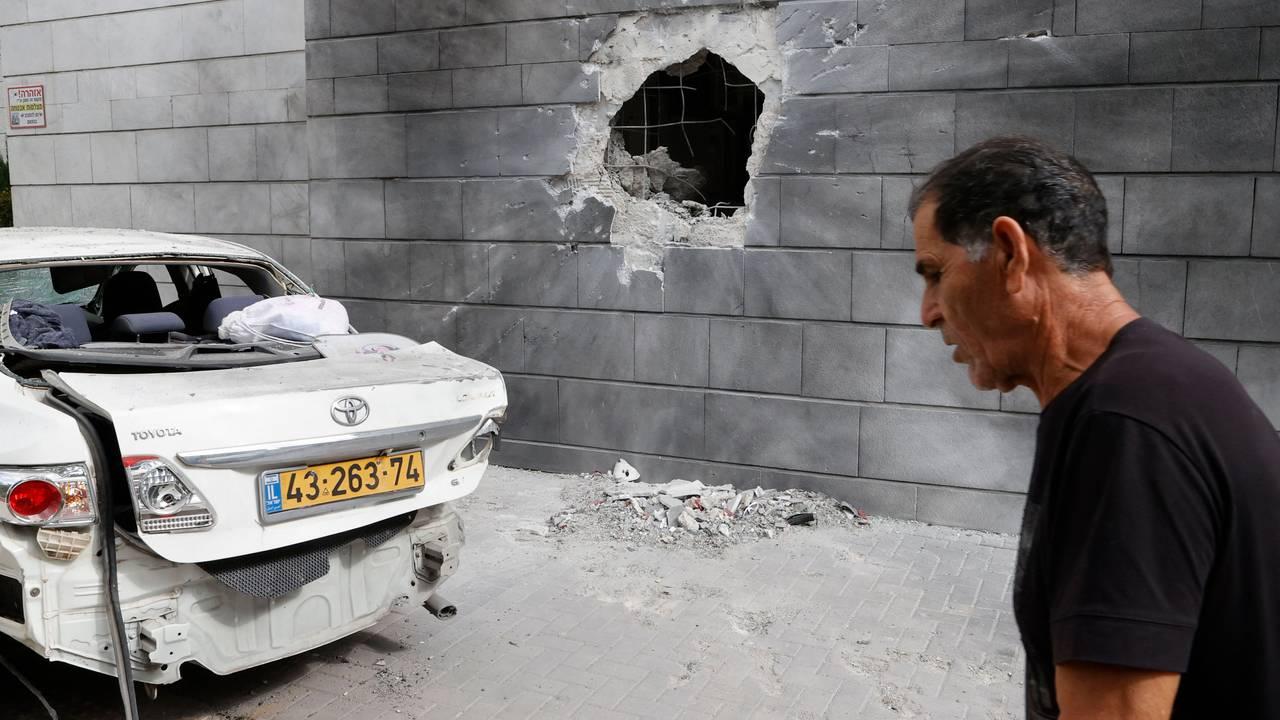 En mann passerer et hull etter en rakett fra Gazastripen traff en mur i byen Ashkelon fredag 14. mai.