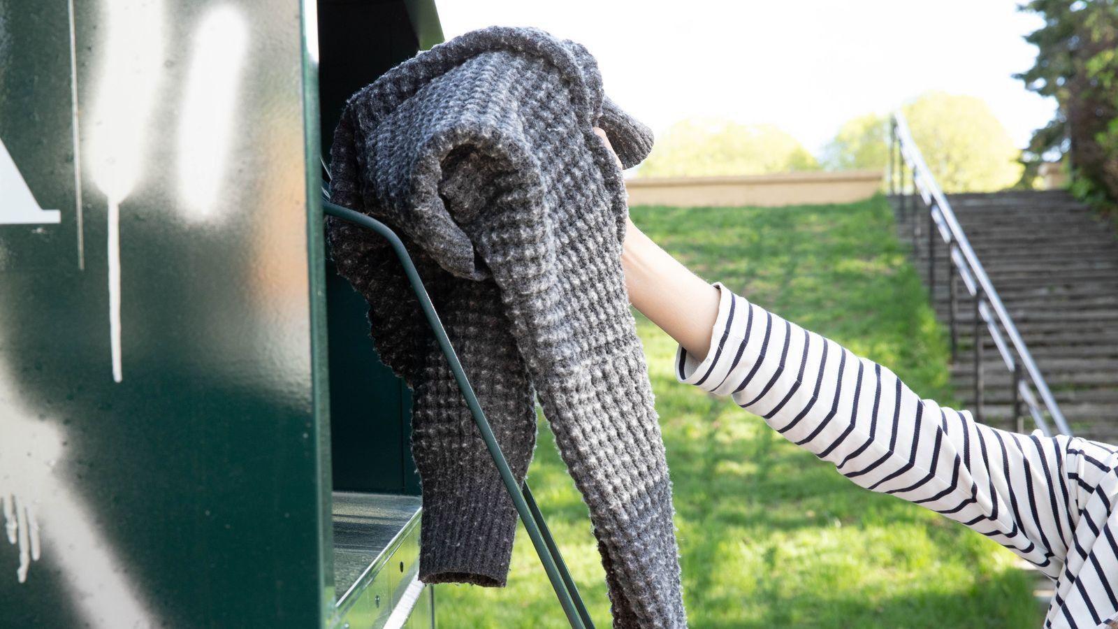 En hånd løfter en grå genser av plast opp mot åpningen på en Fretex-container