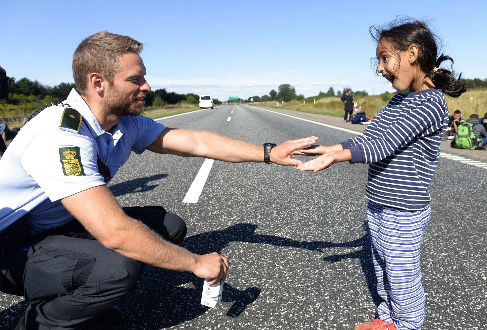 Bildet av en dansk politimann som leker med en ung jente på flukt, gikk viralt denne uka. Flyktningene gikk langs motorveien på vei mot Sverige.