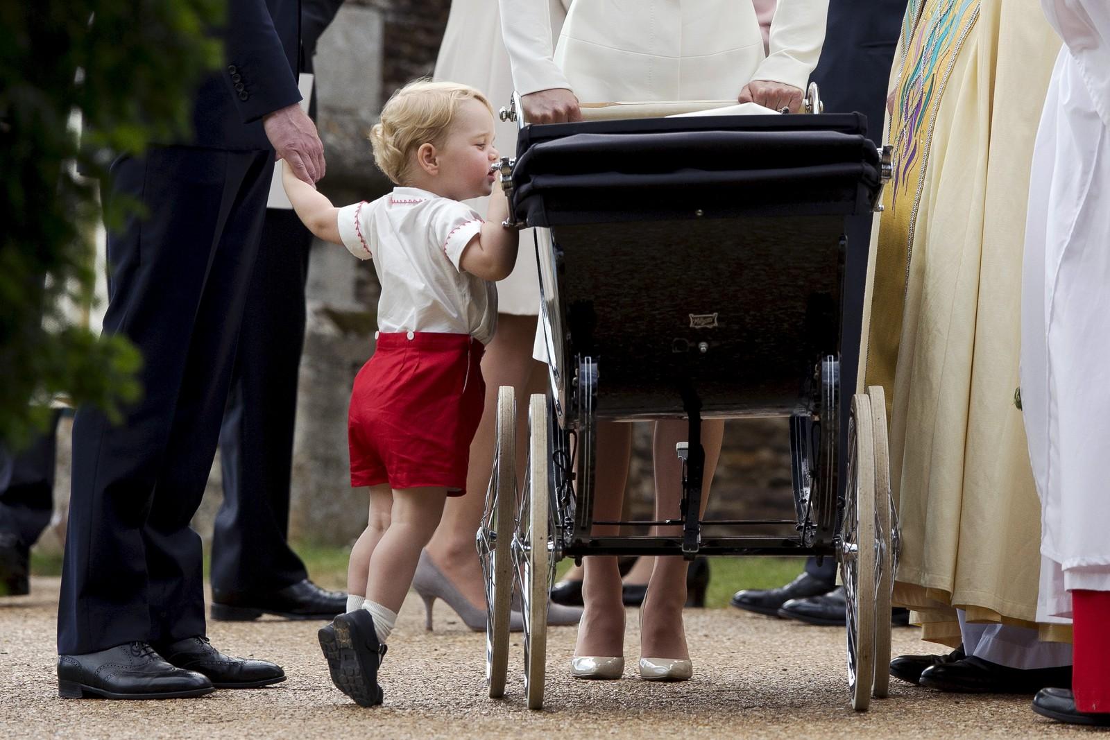 Storbritannias prins George står på tærne for å titte opp i vogna der hans nyfødte søster, prinsesse Charlotte, ligger. Bildet er tatt like etter dåpen i St. Mary Magdalene-kirken i Sandringham søndag 5. juli.