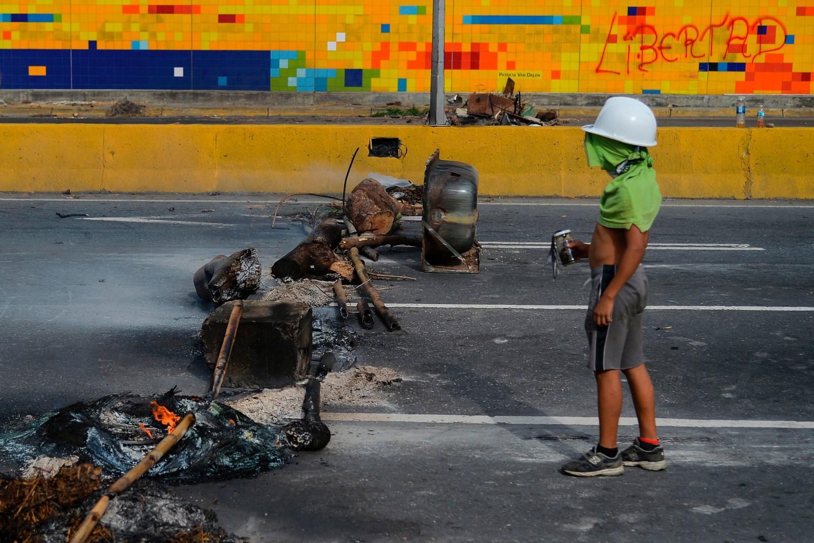 En ung demonstrant ved en veisperring i Caracas. Demonstrasjonene mot president Nicolas Maduro har pågått siden april.