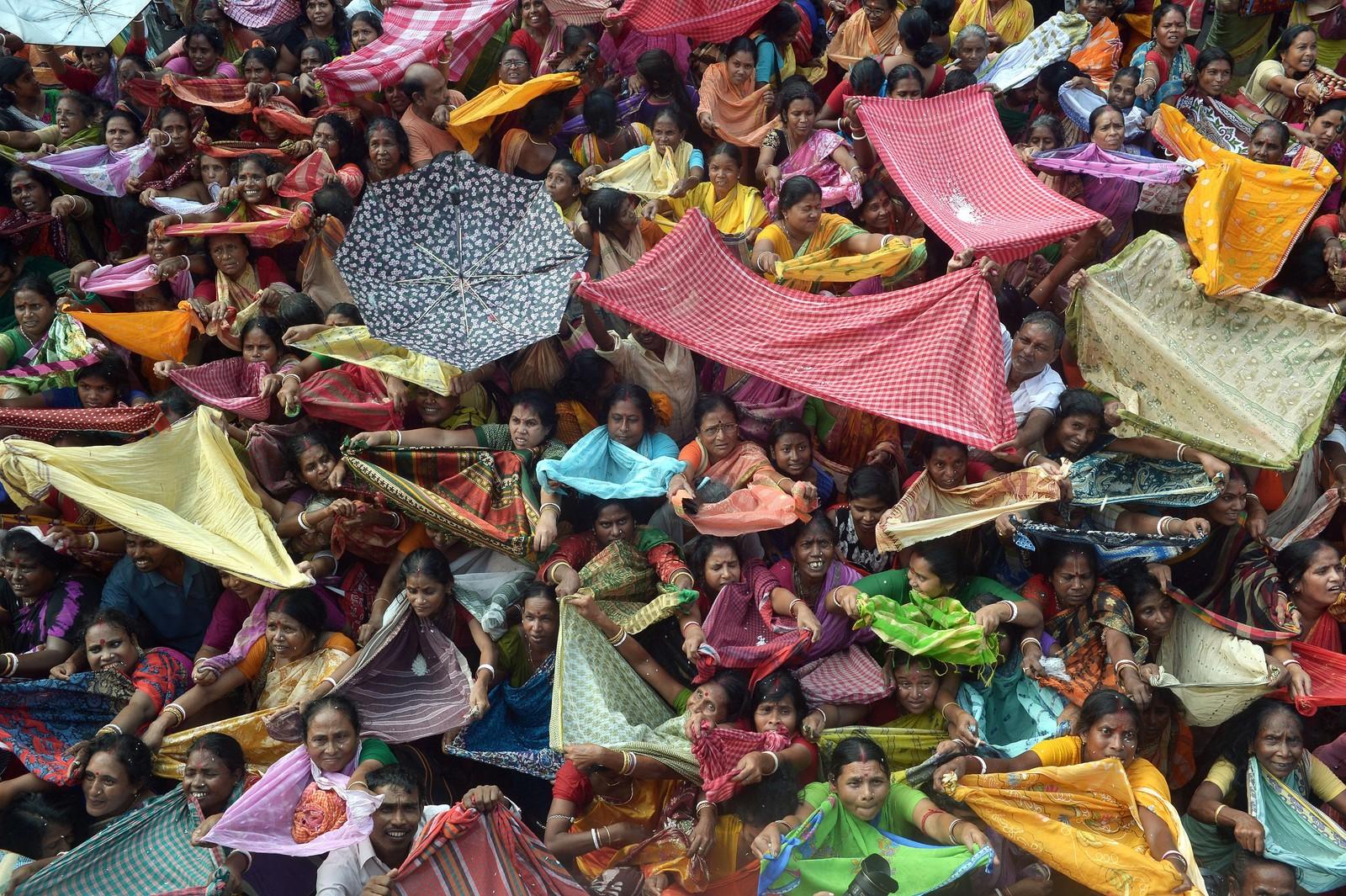 Indiske hinduer samler ris i sjalene sine under en offerseremoni på Annakut-festivalen ved Radha Madhav-tempelet i Kolkata. Den symbolske handlingen skal gi dem god helse og sikre et liv uten sult og fattigdom.