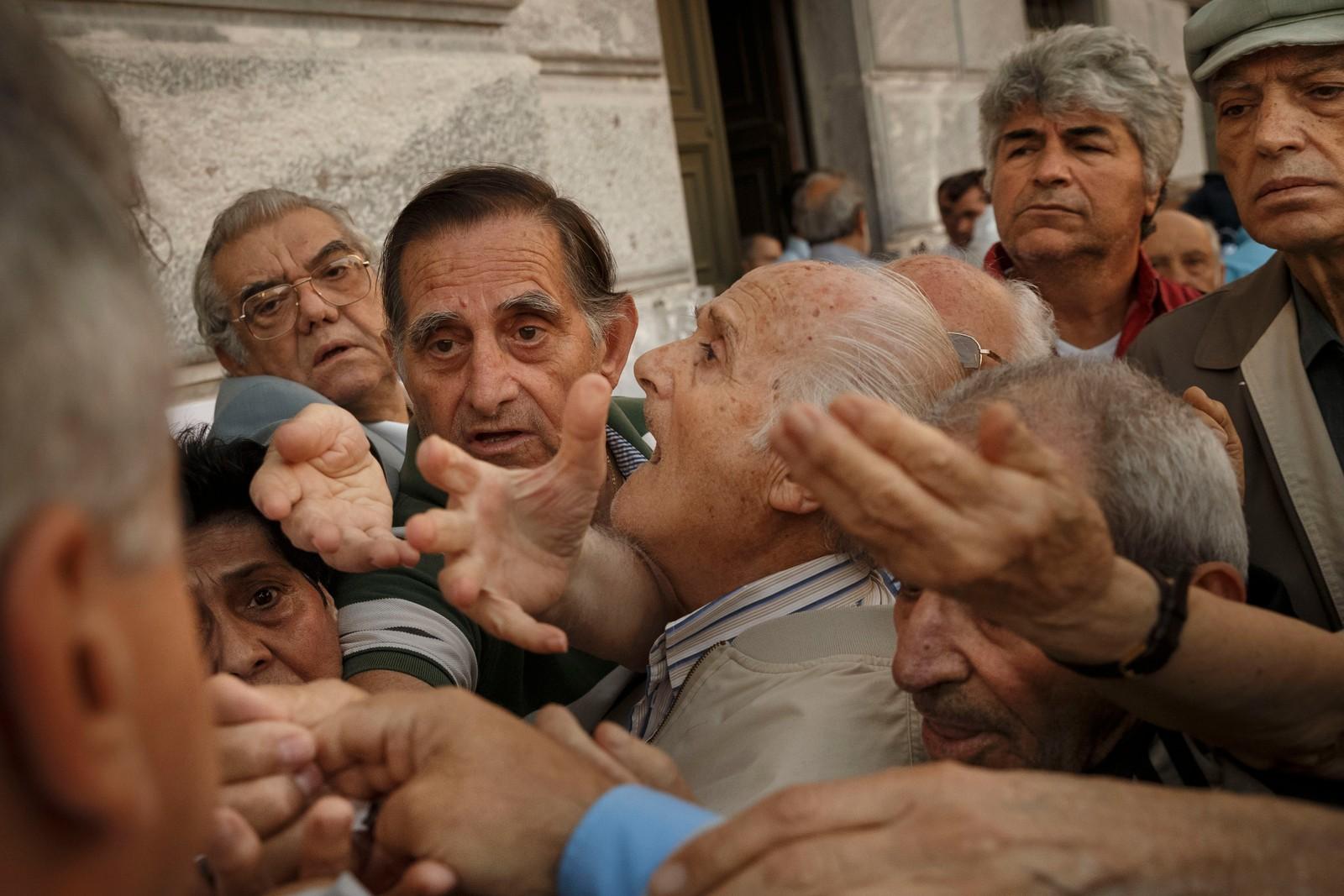 Pensjonister strekker fram hendene for å få tak i kølapper for å komme inn i en bank i Aten.
