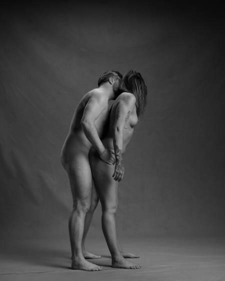 En naken mann med mørkt hår og skjegg står bake en naken kvinne med mørkt hår og tatoveringer. Han holder henne på hoftene og kysser henne i nakken