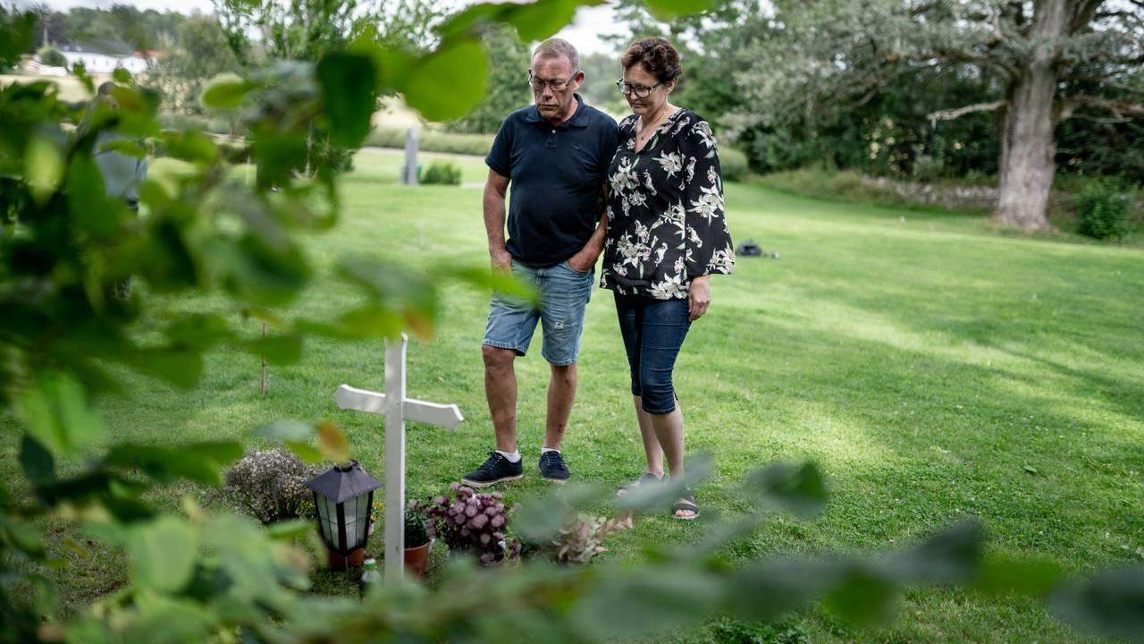 Bilde av foreldrene til Cecilie som står foran graven hennes. De har en alvorlig mine over seg.