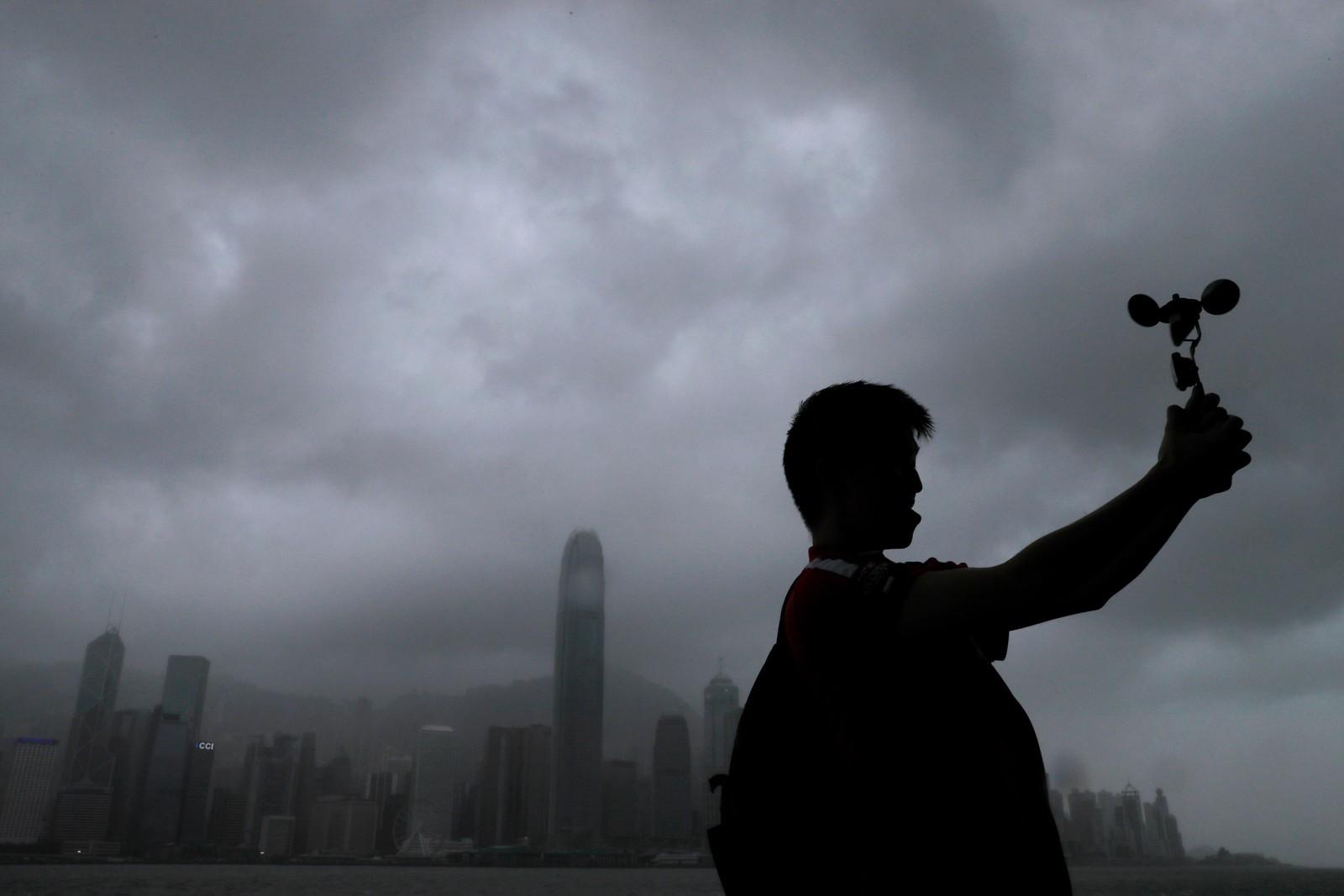 En mann bruker et anemometer for å måle vindhastigheten. Stormen Pakhar førte til kraftig vind i Hong Kong.