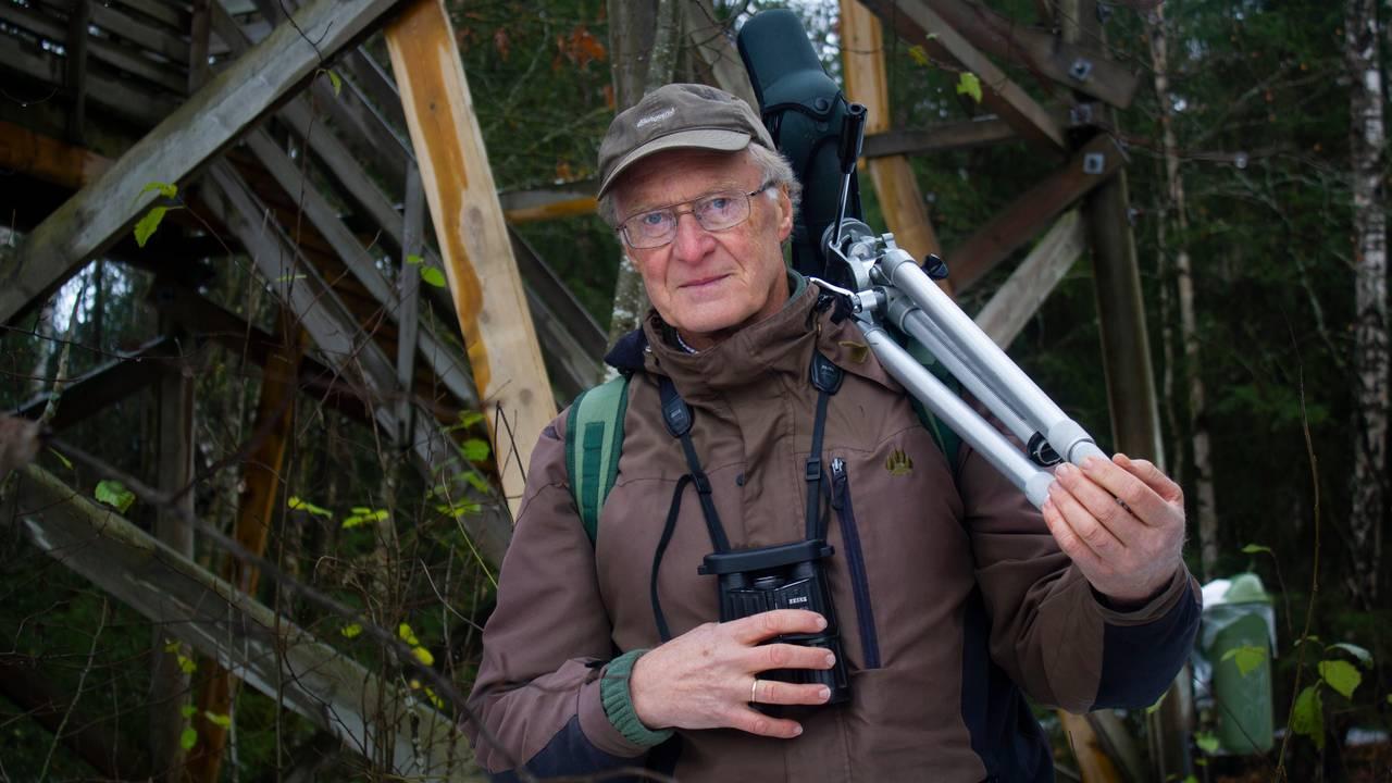 Biolog Jon Bekken bærer på en stor kikkert over skuldrene.