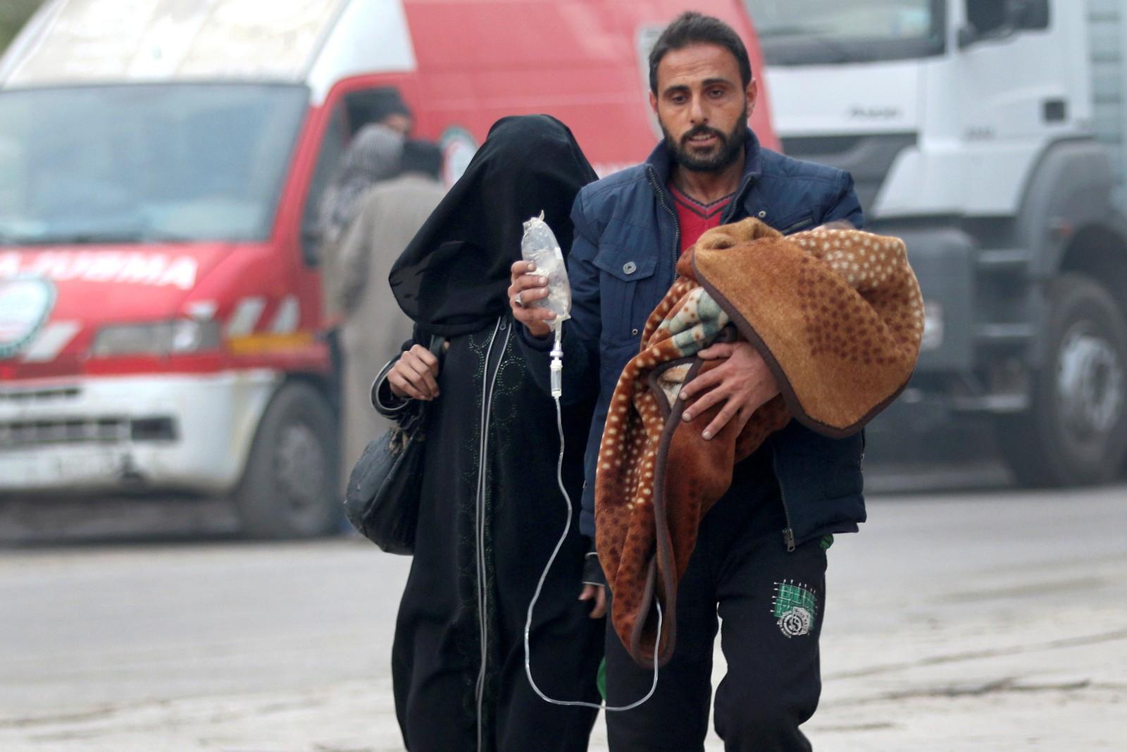 En mann i opprørskontrollerte Aleppo bærer et lite barn som får medisin intravenøst.