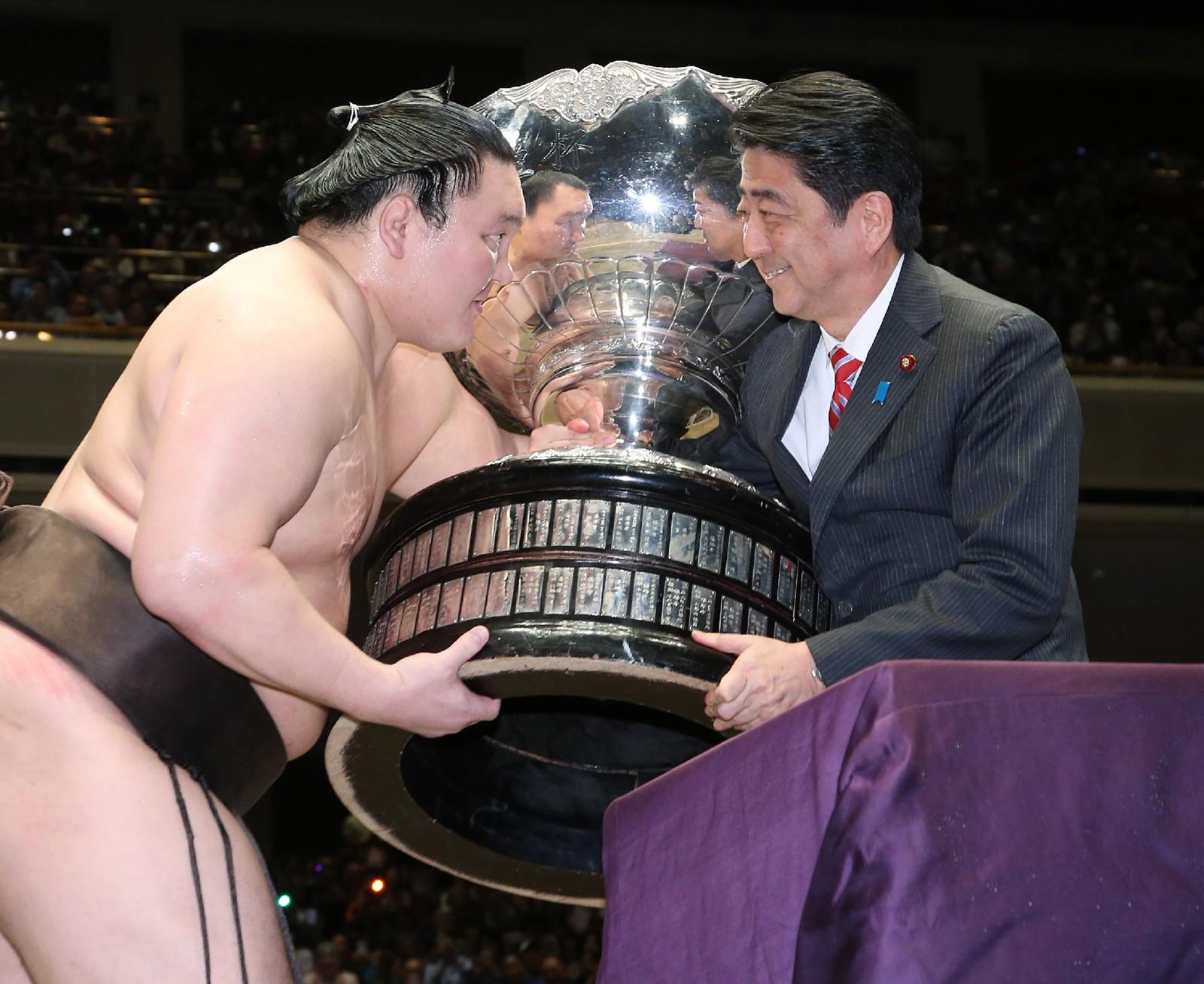 Sumobryter Hakuho (t.v.) mottok vinnertroféet av den japanske statsministeren Shinzo Abe denne uka etter å ha vunnet Grand Sumo-turneringen.