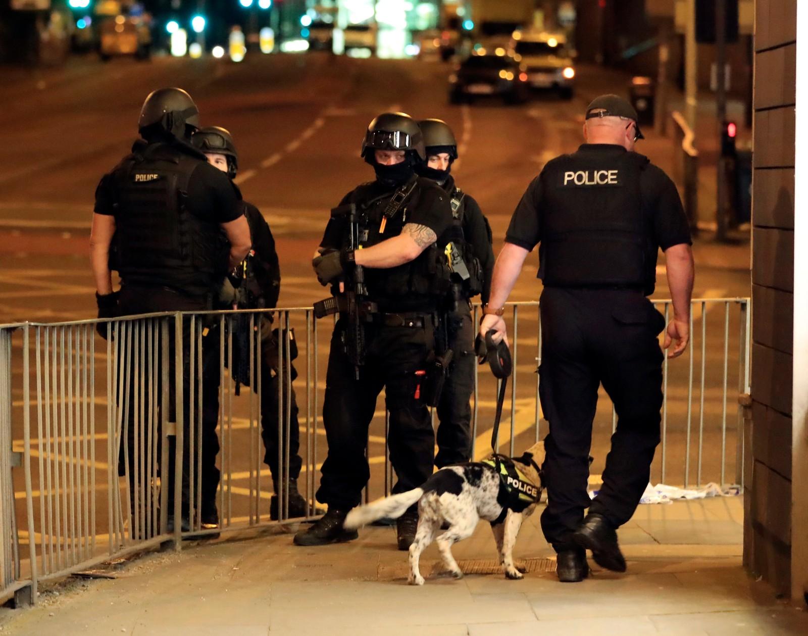 Bevæpnet politi undersøker området med hunder.