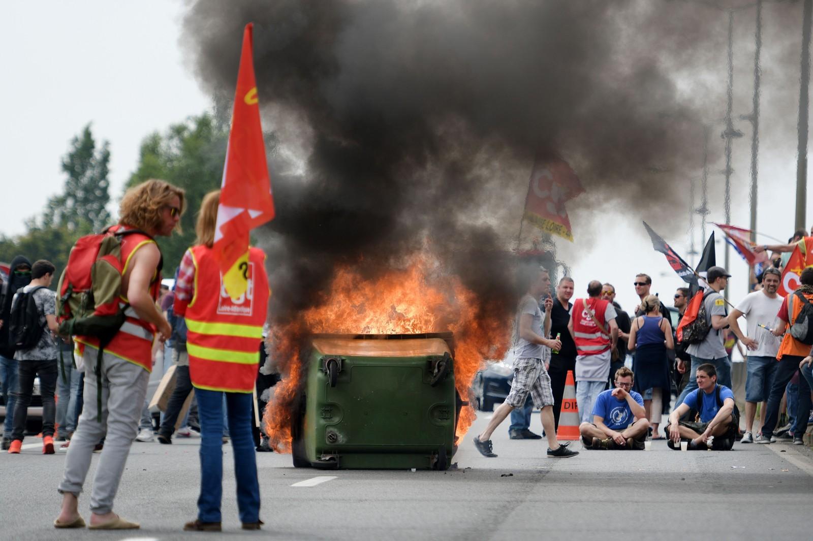 Folk har satt fyr på søppeldunker og bildekk under en demonstrasjon i Nantes i Frankrike. Protestene mot den nye arbeidsloven franske myndigheter vil innføre har vart i to måneder, og fortsetter over hele landet.
