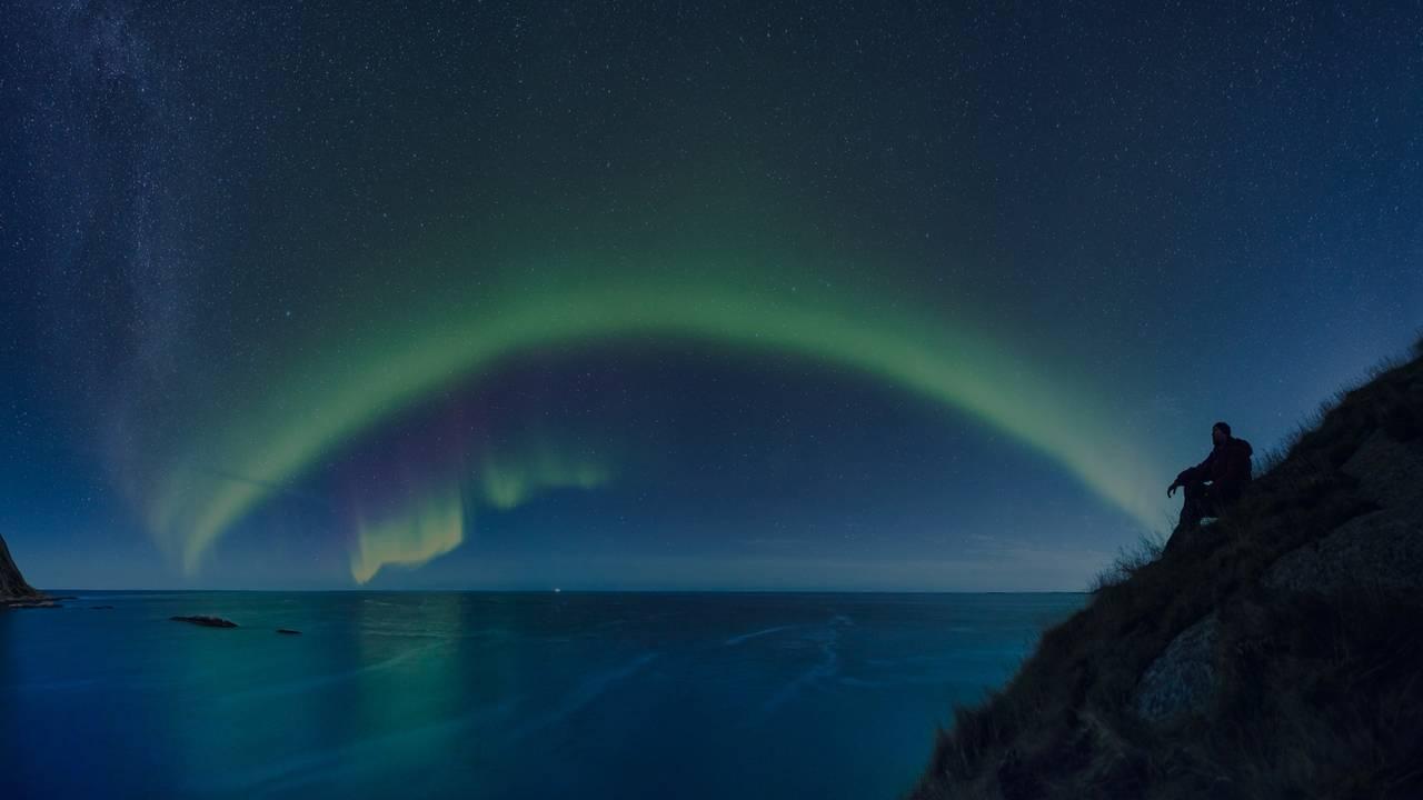 Person sittende på en klippe skuer utover havet på kveldstid. Nordlys spiller på himmelen.