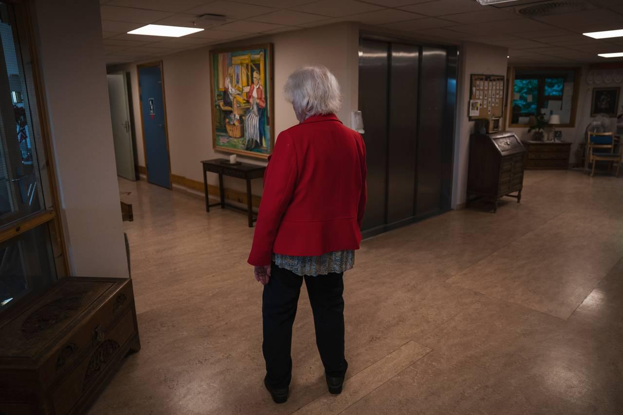 Anne Marie står forvirret i gangen i sin røde jakke og ser mot venstre for å finne ut hvilken vei hun skal gå.