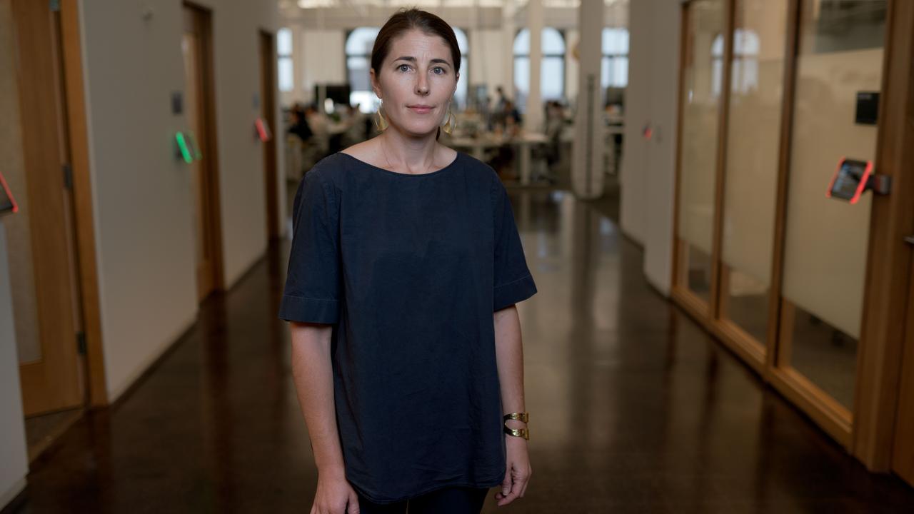 Bilde av Karina Newton, toppsjef for Instagrams retningslinjer. Hun står i en gang, og i bakgrunnen det et kontor med ansatte som jobber. Ansiktsuttrykket er nøytralt.