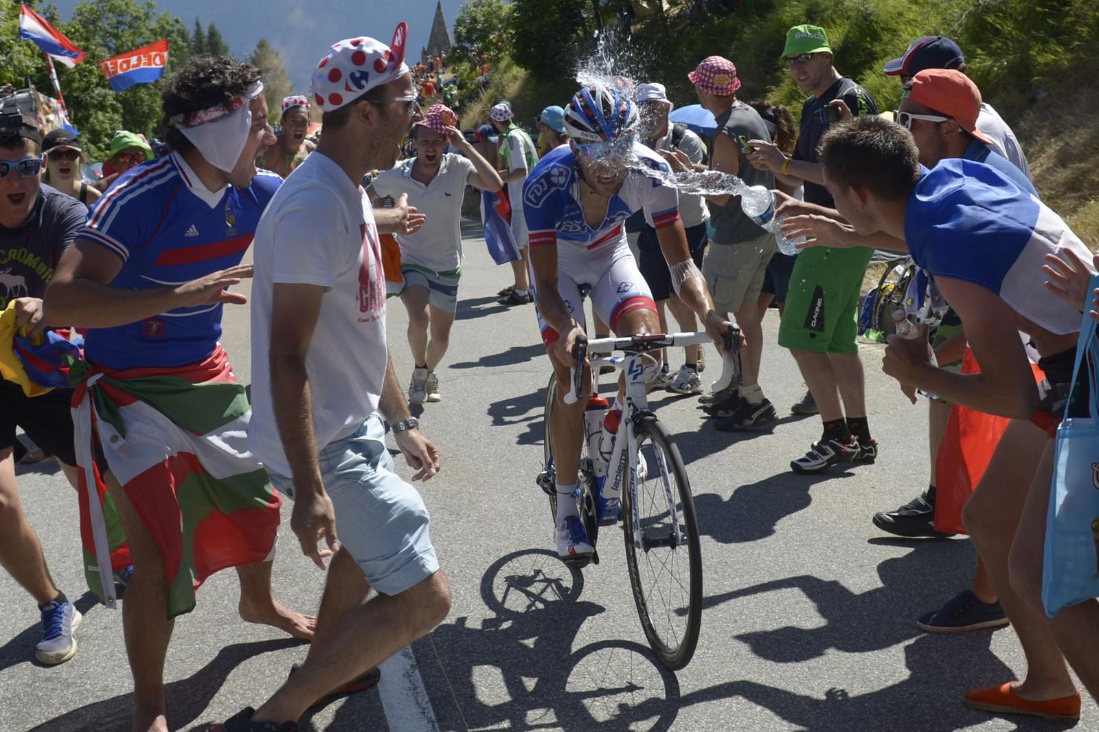 Thibaut Pinot blir kjølt ned av en tilskuer i et brudd på vei opp Alpe d'Huez på den 20. etappen. AFP PHOTO / LIONEL BONAVENTURE