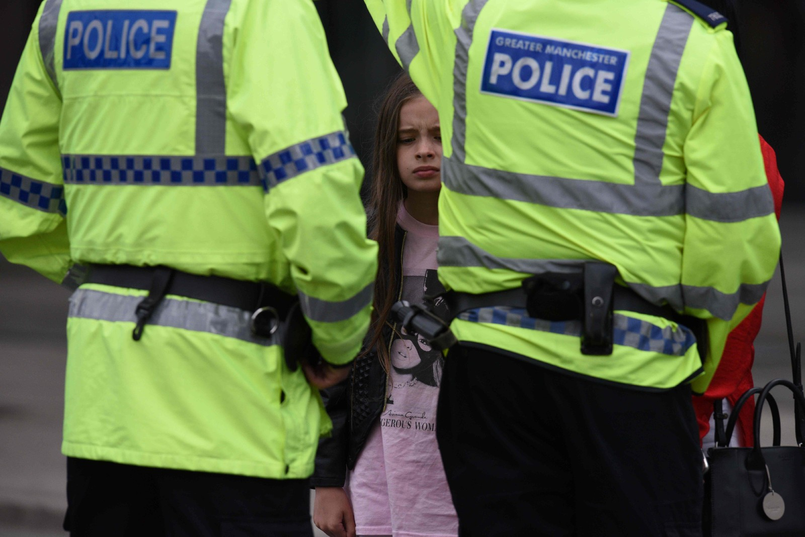 En liten jente med Ariana Grande-skjorte og politi ute på gata.