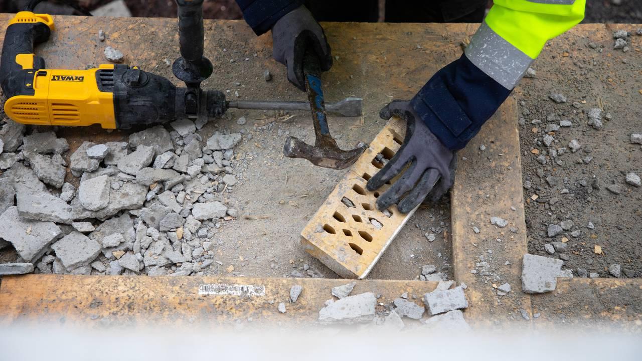 Vi ser et arbeidsbord ovenfra. I ytterkanten av bildet ser man hendene og den signalgule jakken til rivearbeideren som jobber med å pusse og rengjøre murstein.