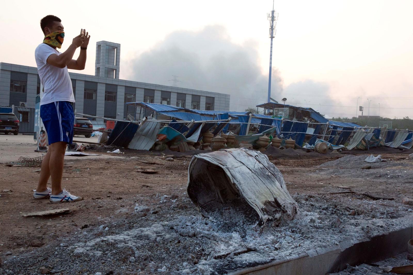 DAGEN DERPÅ: En man tar bilde av skadene etter den enorme eksplosjonen utenfor Tianjin.
