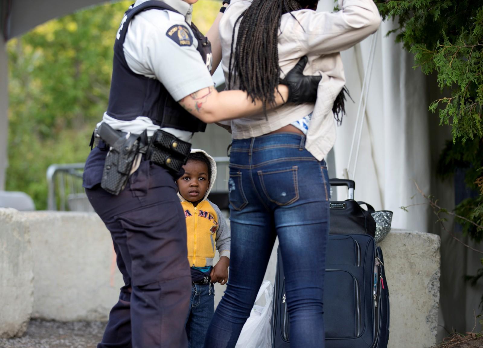 Evanston (2) ser på mens kanadisk grensepoliti sjekker moren hans etter at familien krysset grensen fra Champlain, New York i USA til Lacolle i Canada fredag. Familien hevder de er fra Haiti.