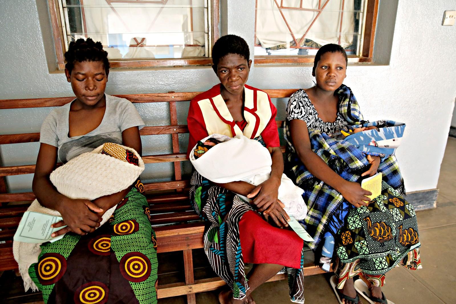Disse tre kvinnene nyter godt av det norsktyske bistandsprosjektet på Helsestasjonen Mbela i Balaka-distriktet sør i Malawi. De holder på sine nyfødte babyer og kortene med påskriften Resultbased financing. Gjennom prosjektet får de penger for å komme til klinikken for å føde. Pengene skal dekke transporten til sykehuset og mat og andre nødvendigheter i dagene de er der. Tilgang på helsehjelp før, under og etter fødesel er avgjørende for at tusenårsmålet nåes.
