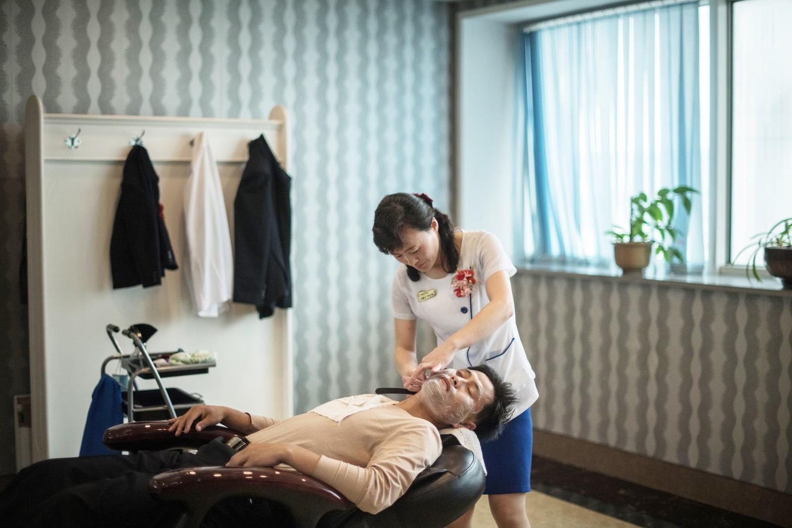 En mann blir barbert i en frisørsalong i Pyongyang.