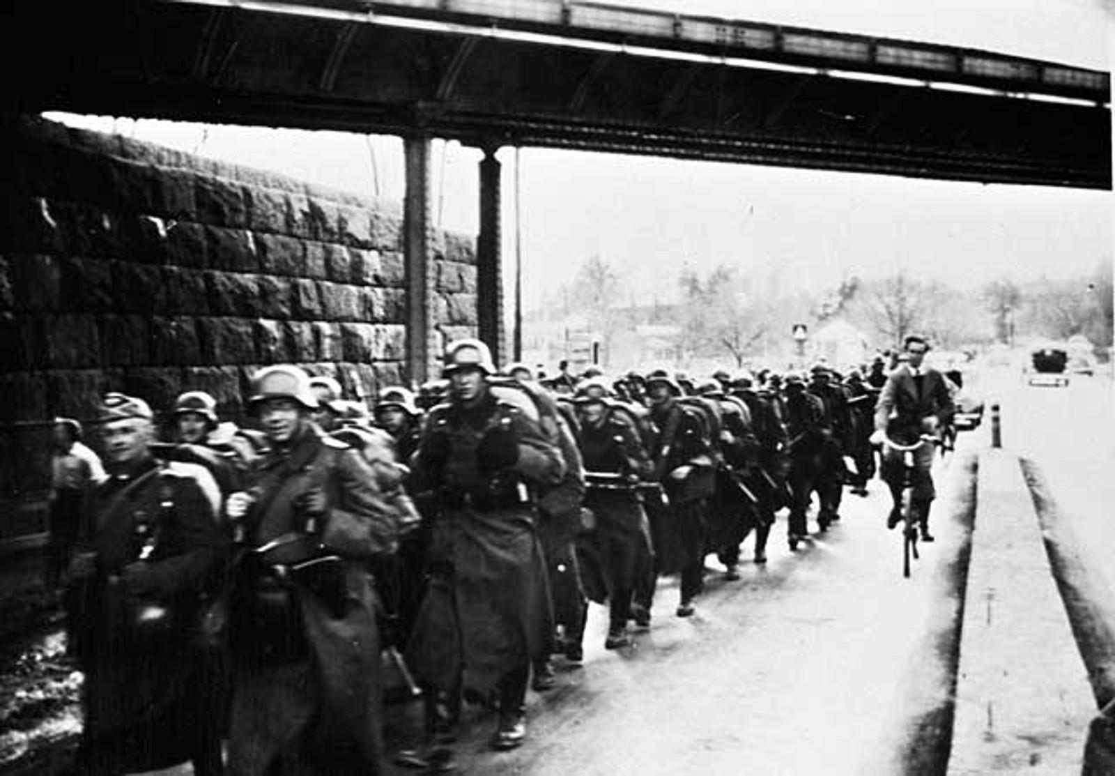 PÅ NESTTUN: Tyske styrker marsjerer under jernbanebroen på Nesttun.